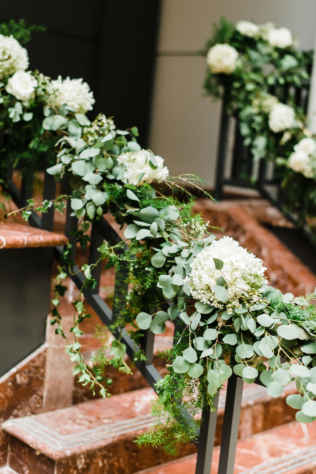 Hydrangeas, white roses and silver dollar eucalyptus cascading down the entrance staircase at The Goodwin Hotel - Pearl Weddings & Events