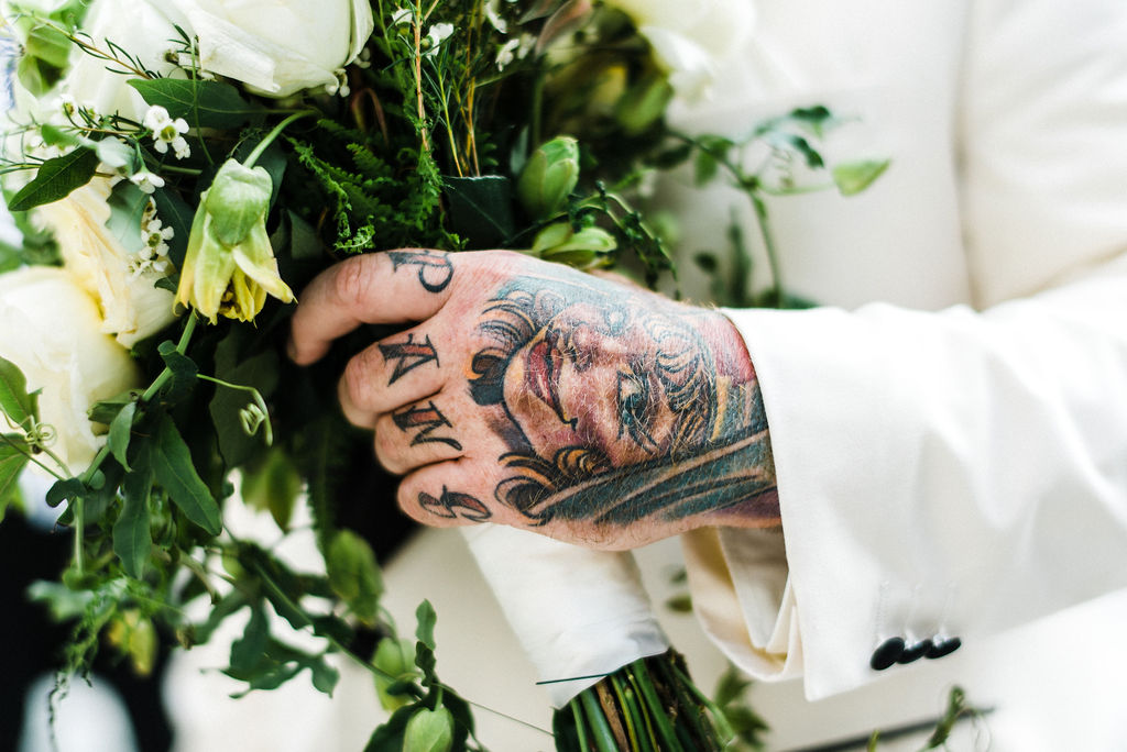 Grooms tattooed hand holding his wife bouquet filled with passion flowers - Pearl Weddings & Events