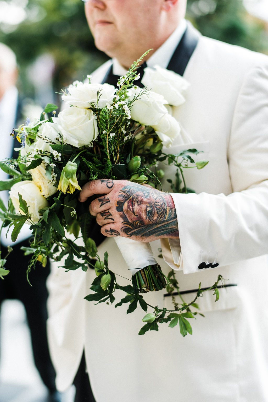 Tattoos and bridal bouquets have never looked so good! Groom, Tyler Anderson is in his all white Vera Wang suit holding his wife's bouquet by Ruth L. - Pearl Weddings & Events