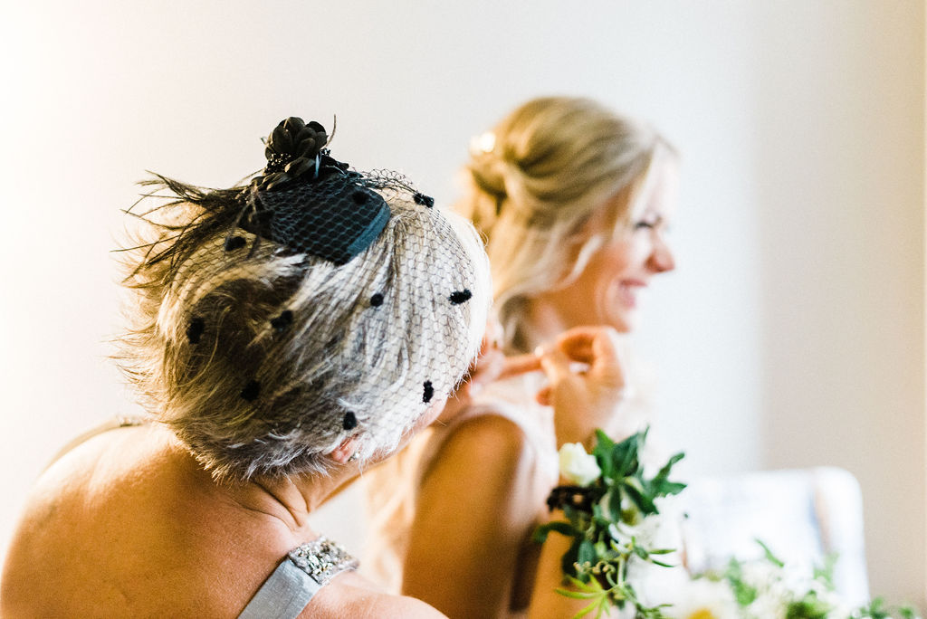 Mother of the bride helping the bride get ready for her wedding ceremony at a Great Gatsby themed wedding in Hartford, CT - Pearl Weddings & Events