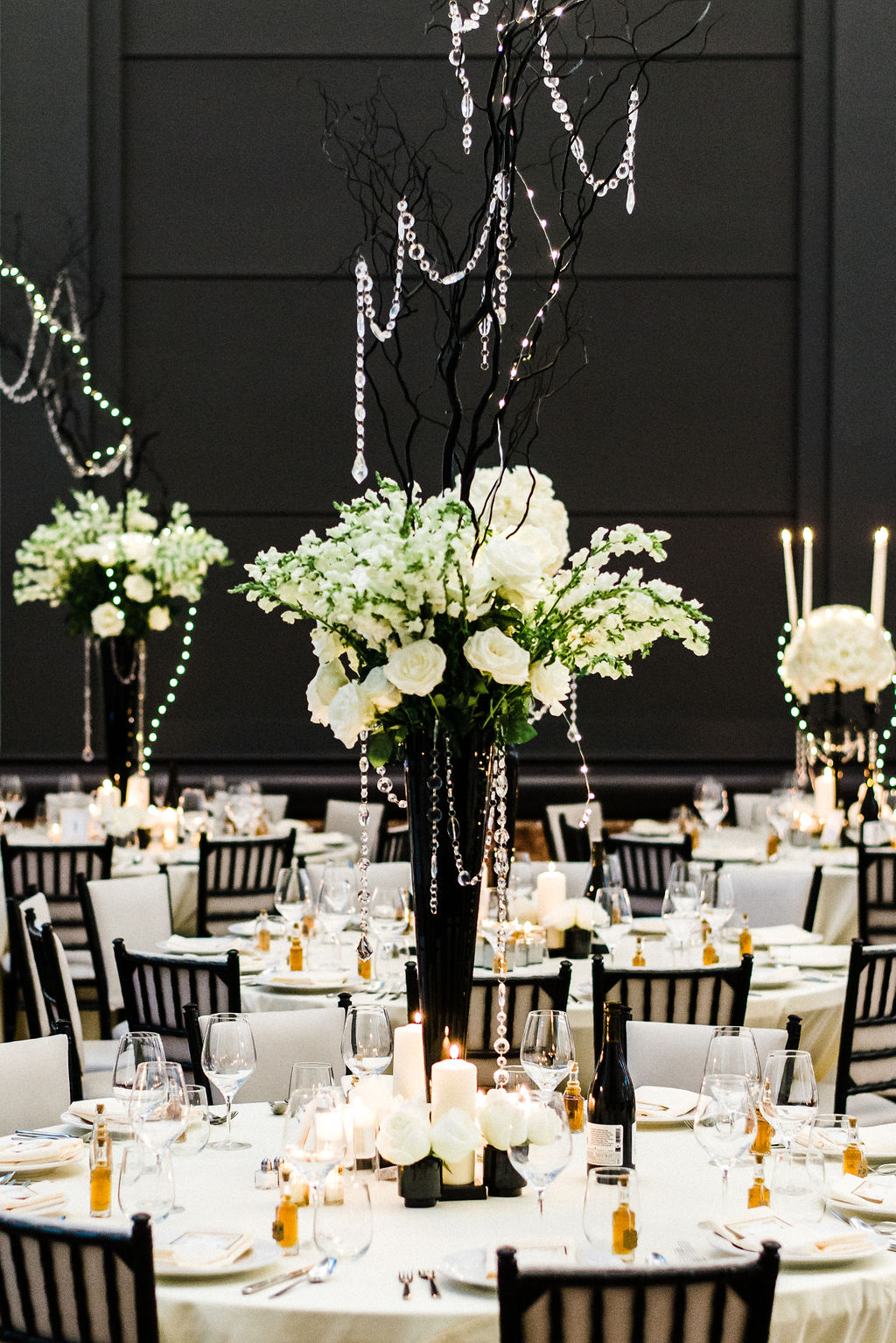 Tall black glass vases and white roses as the wedding centerpieces for a Great Gatsby themed wedding - Pearl Weddings & Events