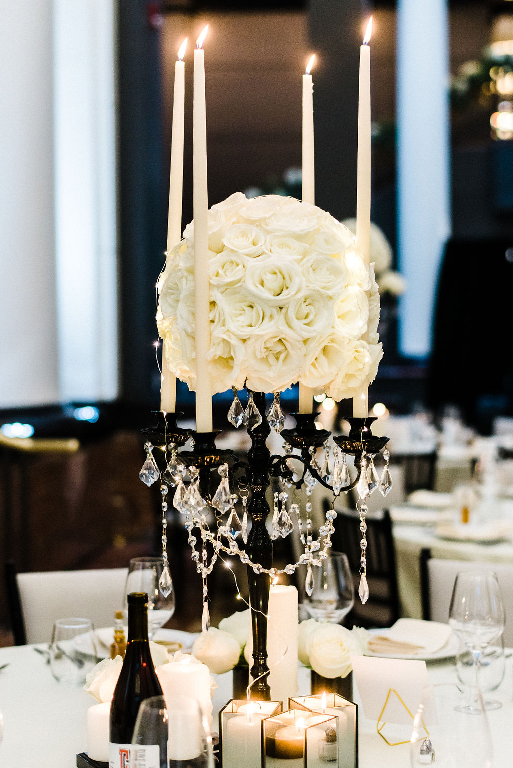 Floral centerpieces designed by Ruth L. White roses on a black candelabra with ivory candle stick and hanging jewels - Pearl Weddings & Events