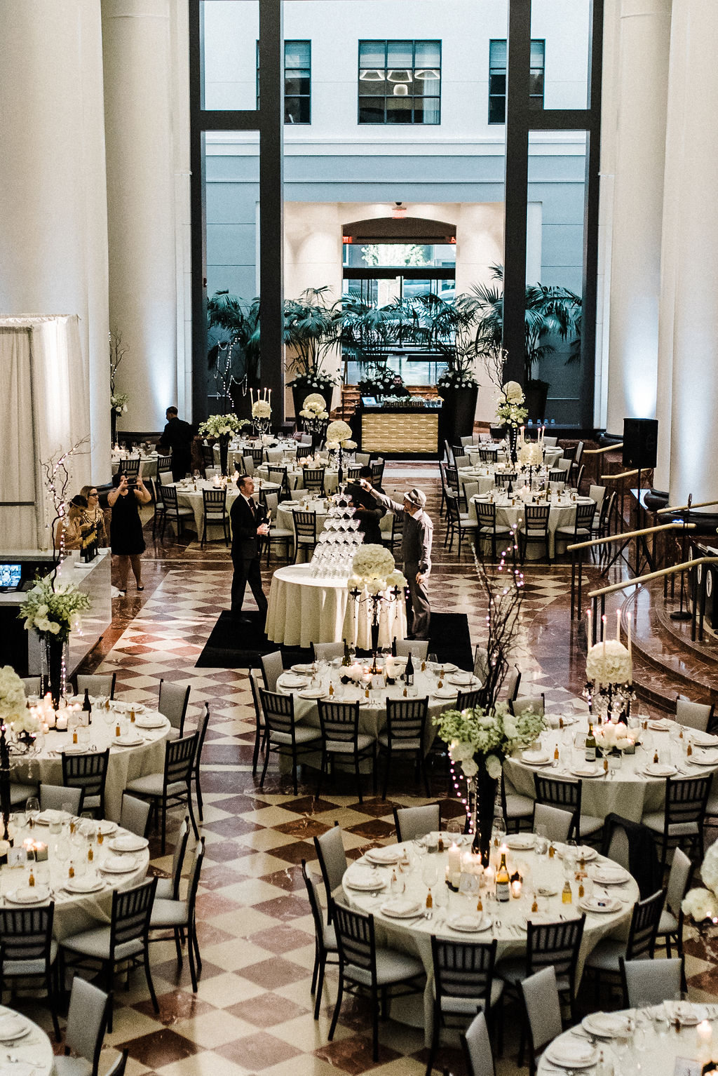 Beautiful floor plan white round tables and a champagne tower being poured as the bride and groom enter - Pearl Weddings & Events