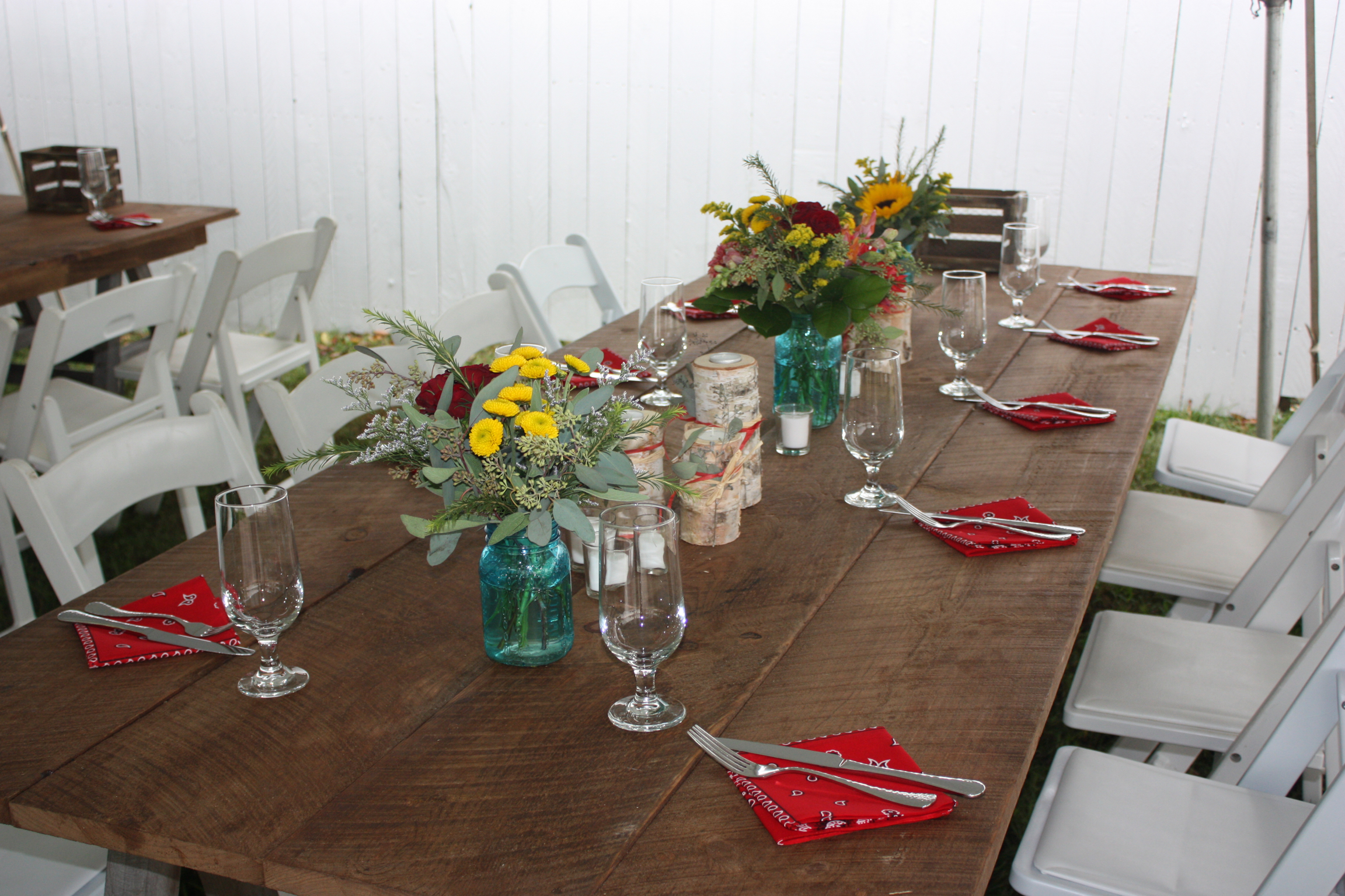 Red napkins, farm tables, white garden chairs and blue mason jars with sunflowers for this rustic backyard wedding - Pearl Weddings & Events