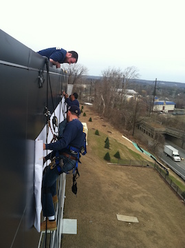sign installers rappelling off of building