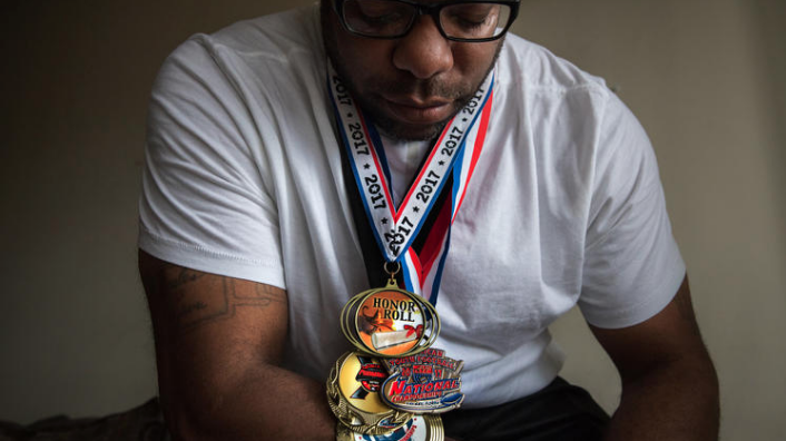 Ronald Hagan, posing with medals of his son Ryan, who completed suicide in November. (photo: Chicago Tribune)