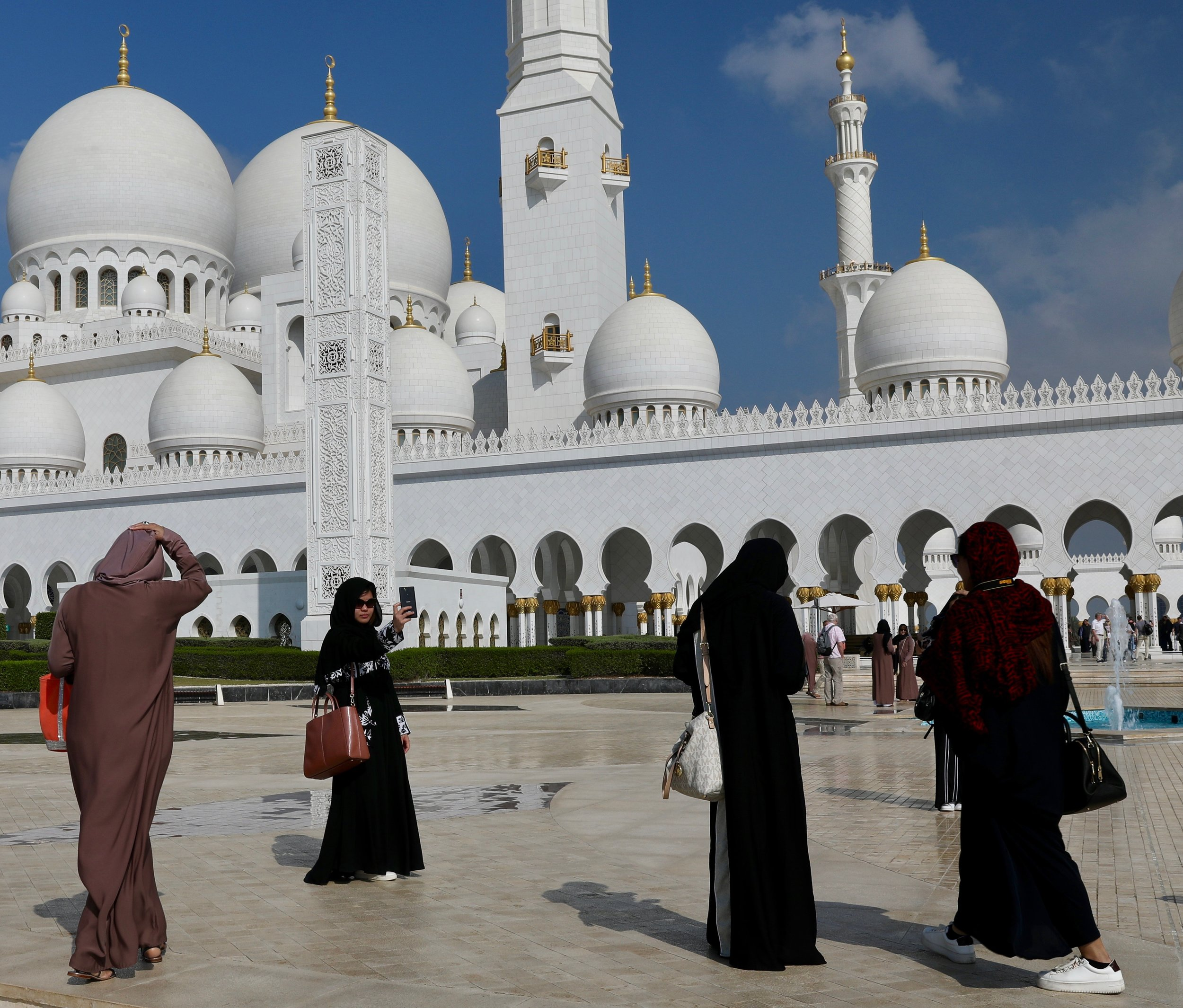 a woman takes a selfie outside of the grande mosque