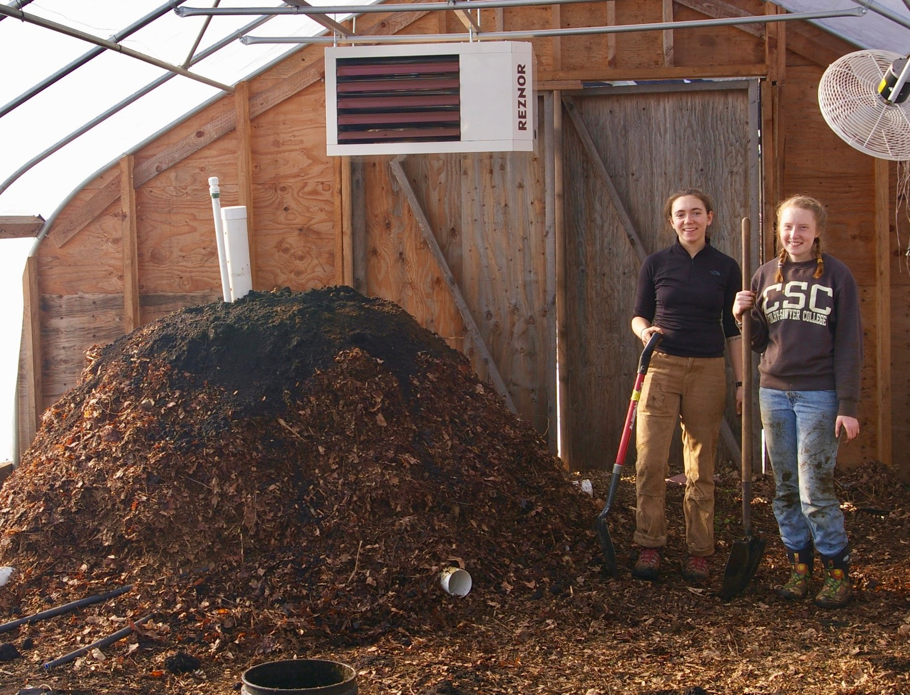 Colby-Sawyer College students experiment with compost as a source of heat for winter growing.
