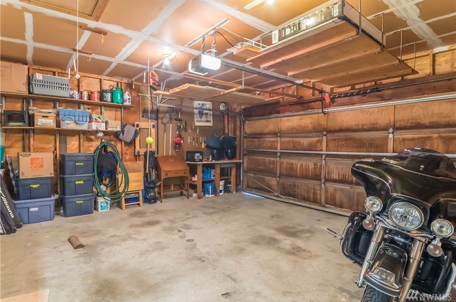 Garage is clean and provides shelves to keep things organized.