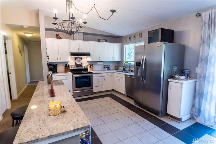 A convenient kitchen with bright cupboards, an easy to clean tile floor, and great appliances.