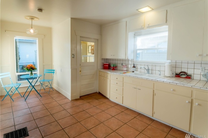 Tiled kitchen with breakfast nook, plenty of cabinets, and exit through the mud room to the backyard.
