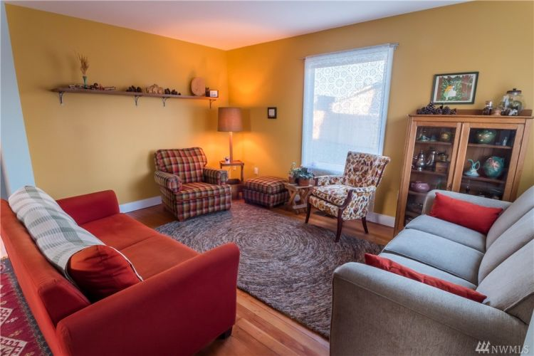 Living room is just outside kitchen with 2 large windows, and lovely fir floors.