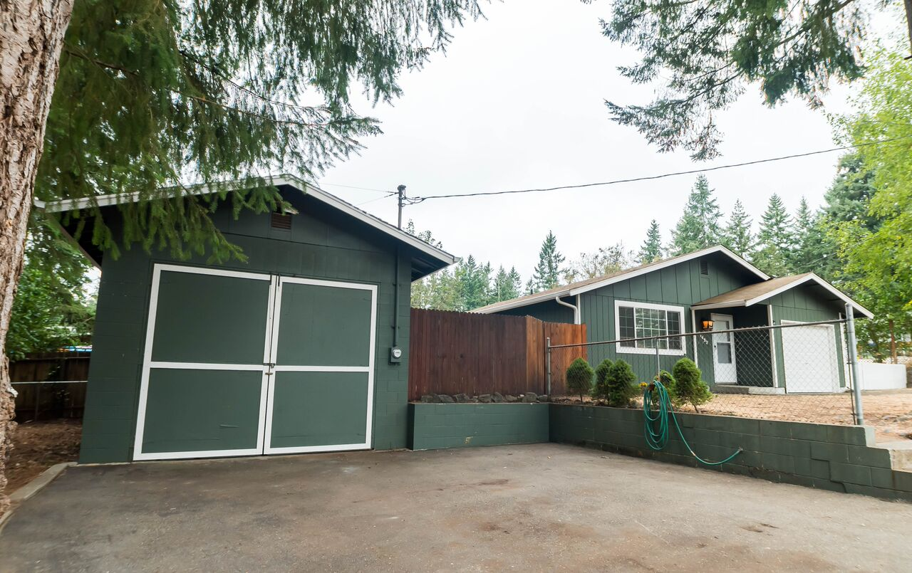 Side drive leads to detached garage/workshop with plenty of space for building, repairing, and storing.