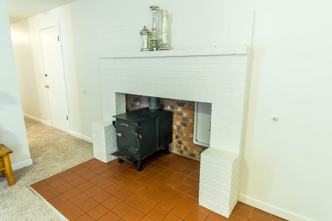 Cozy wood stove and mantle perfect for photos and decorations.