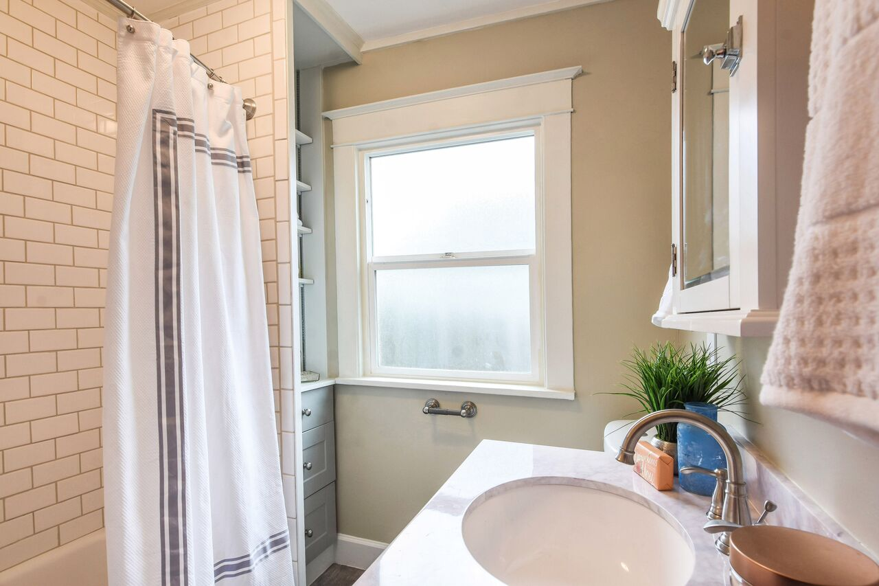 Updated bathroom with white subway tile to the ceiling. Shelves and draws make great use of the space in the corner near the window.