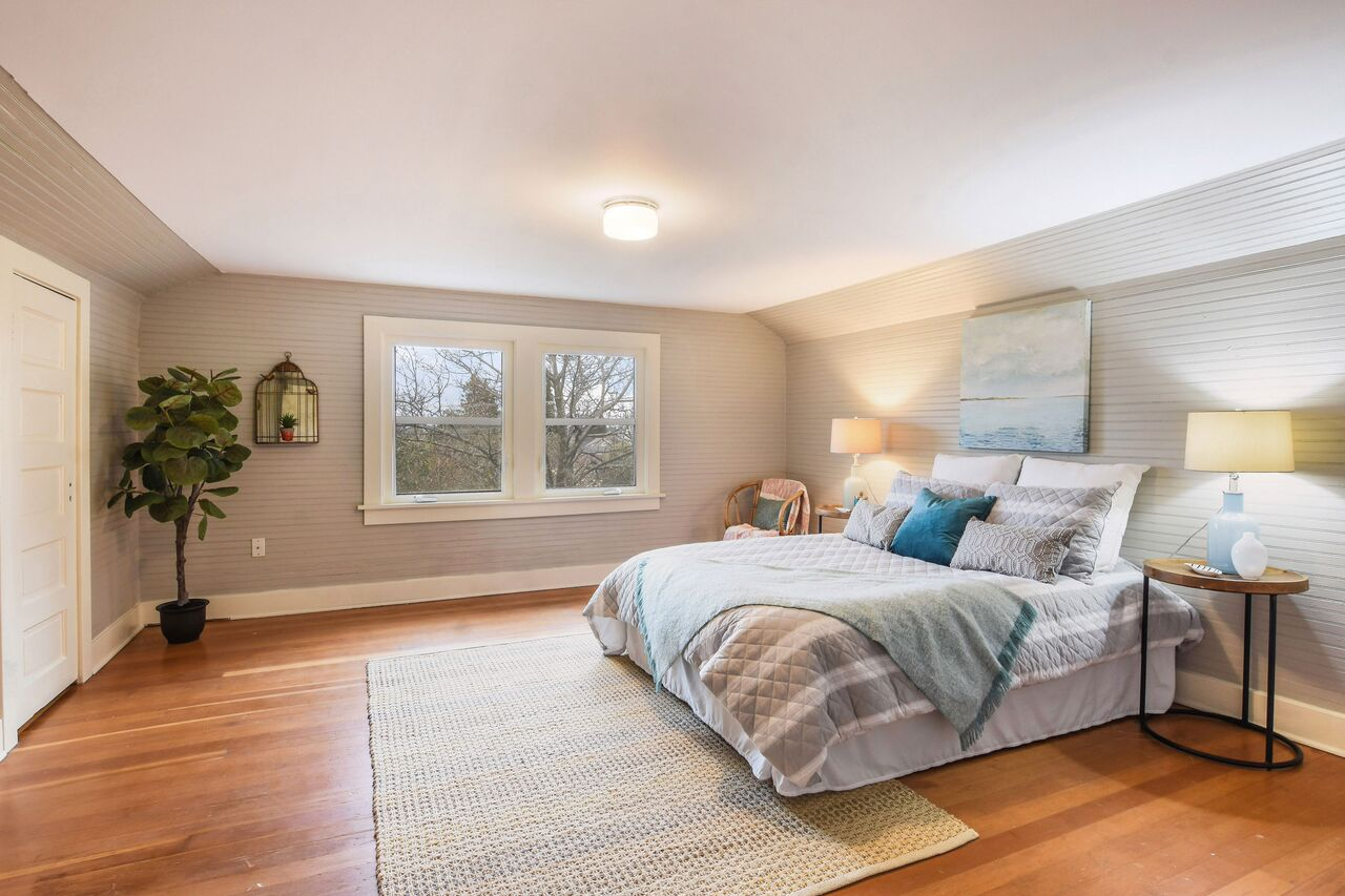 Second floor bedroom with simple, classic details, and warm tones from the original fir floors.