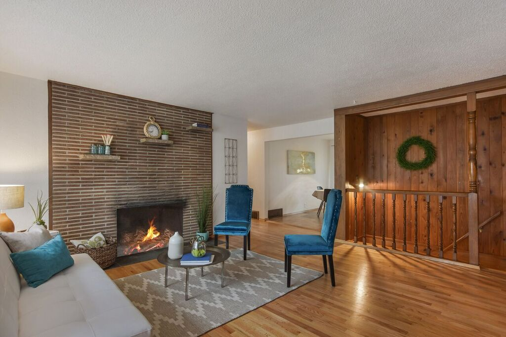 Oak hardwood floors, brick hearth, and beautiful paneling in the bright living room.