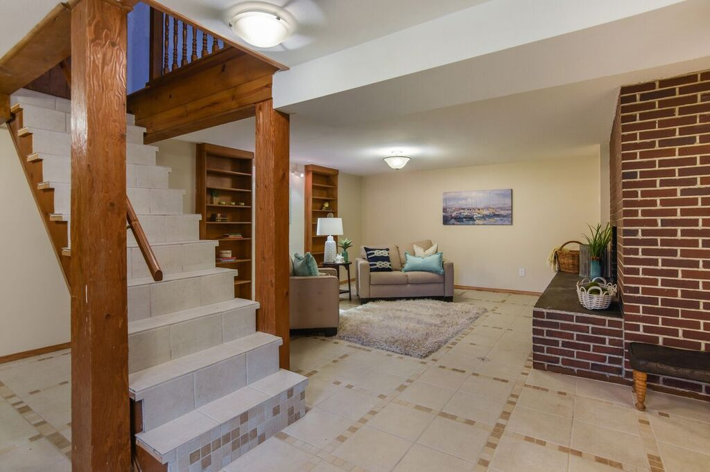 Fully finished daylight basement is spacious with wooden shelves, and a beautiful brick hearth area.