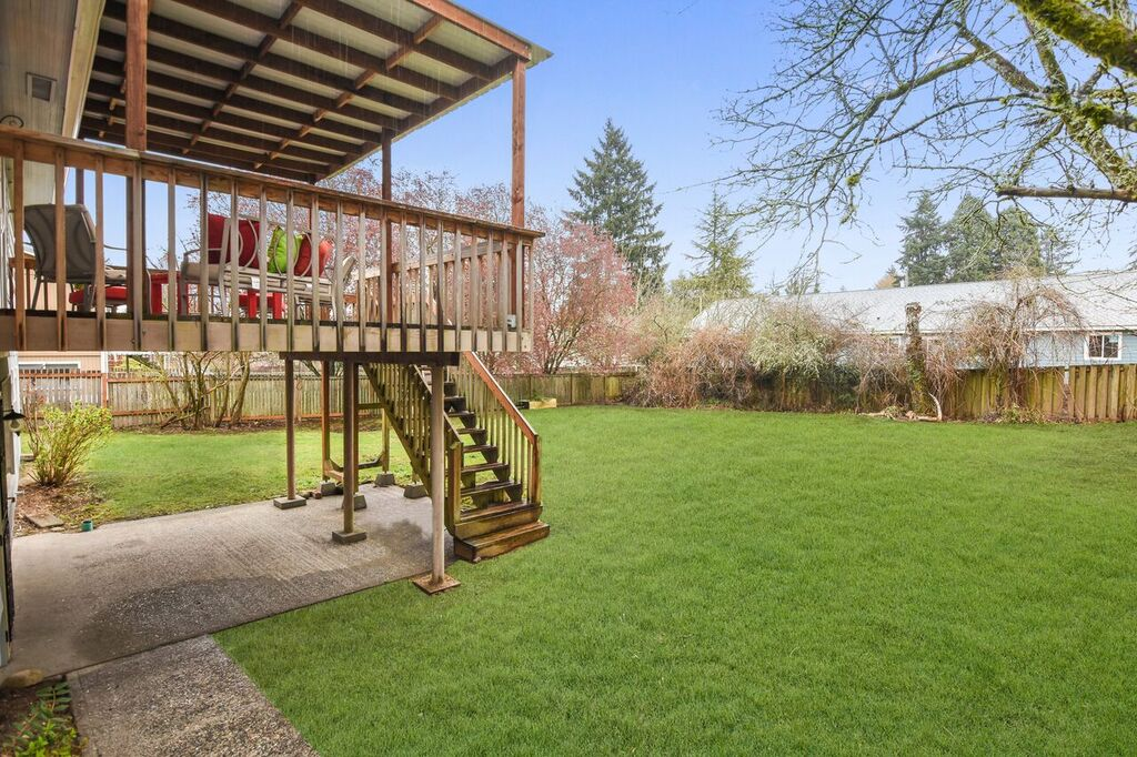 Big fully-fenced backyard with lawn and patio.