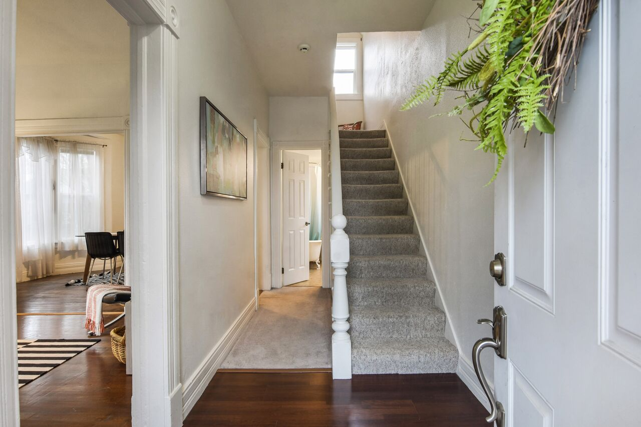 Entrance with open staircase leading up to 2 bedrooms, and hallway to the full bathroom (just a glimpse of the clawfoot tub!).