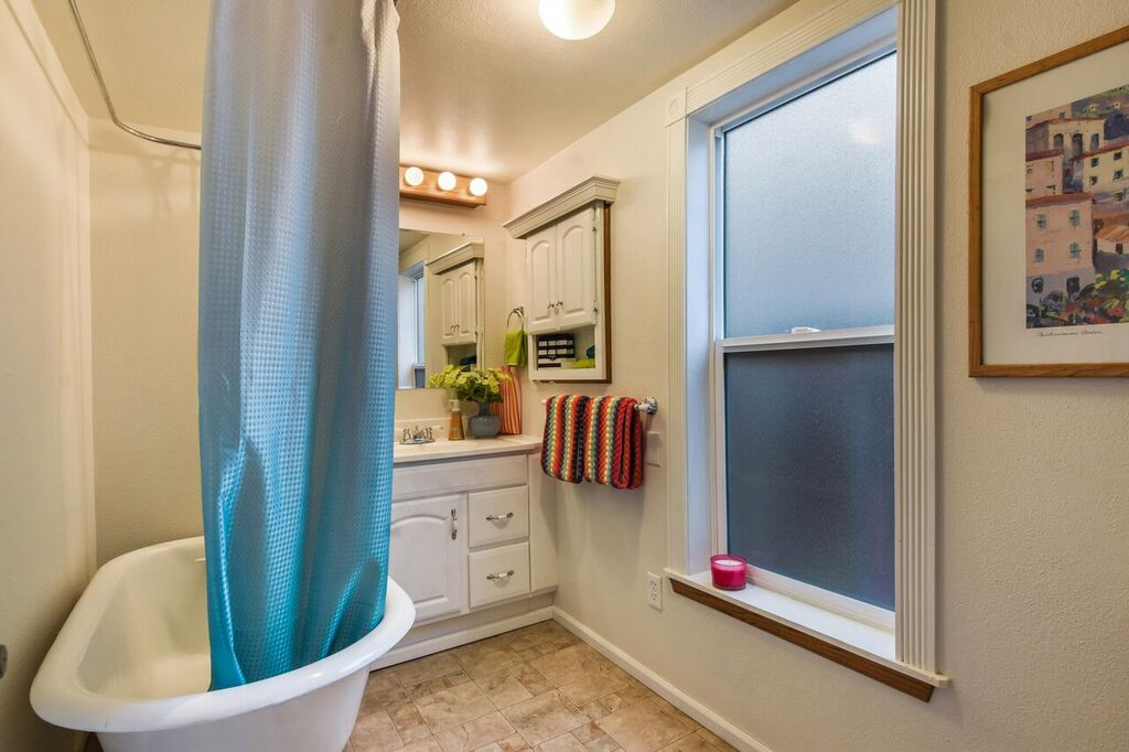 Full bath with clawfoot tub and shower, vanity, and vinyl floors.