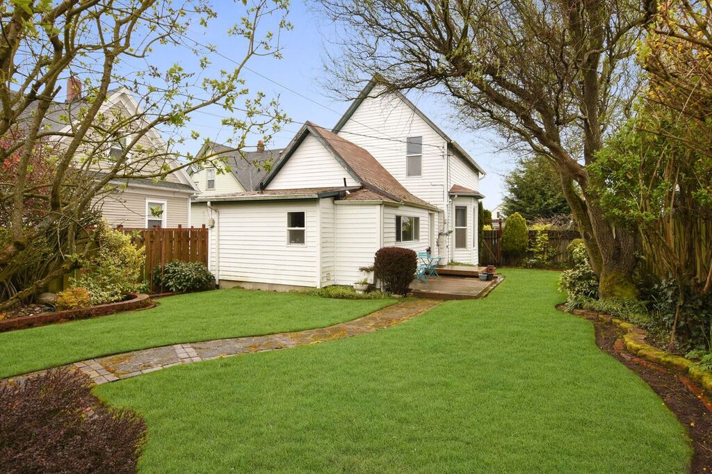 Backyard with edged lawn, paved path, and mature landscaping.