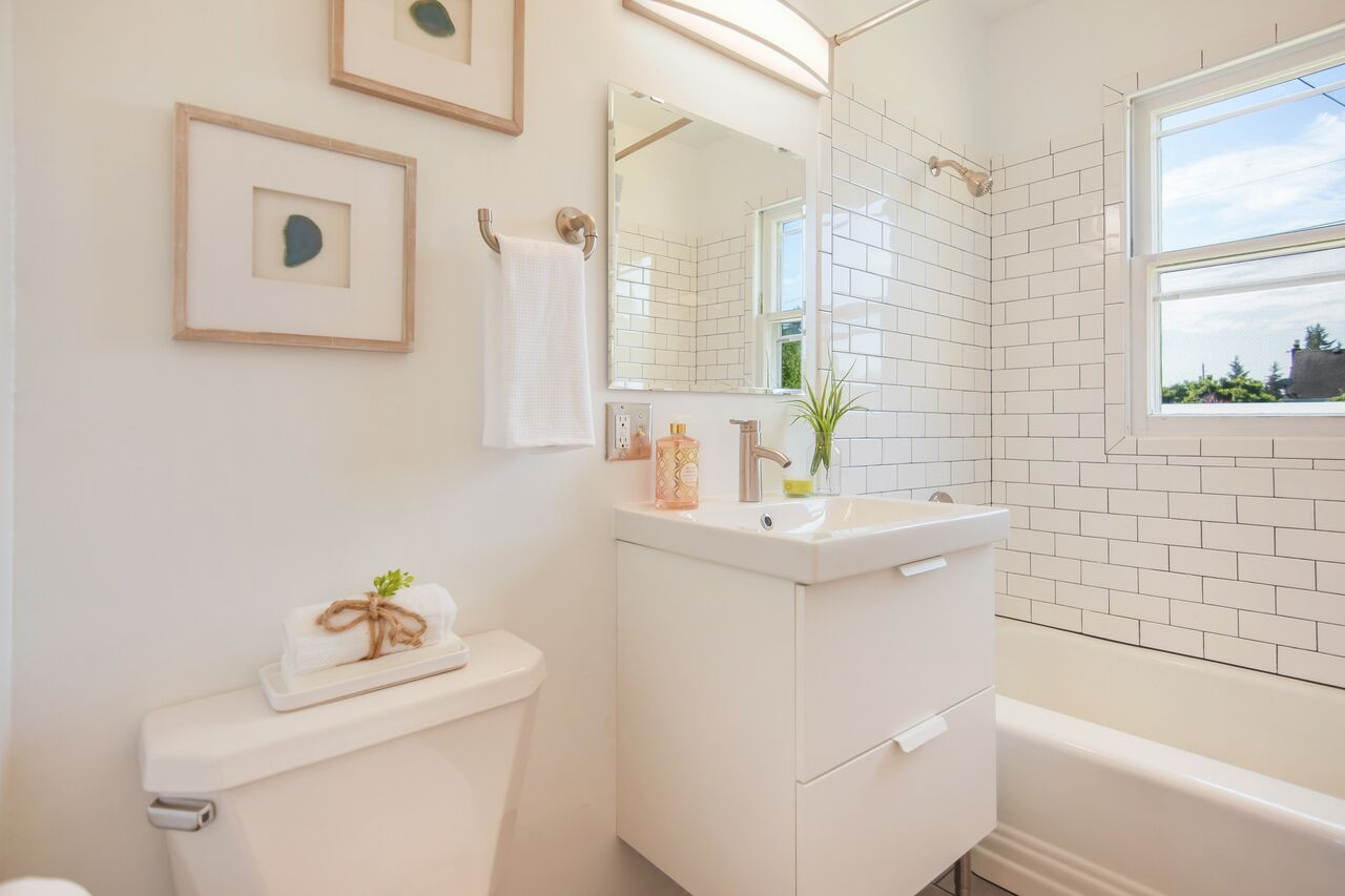 The updated full bath just outside the bedrooms features subway tile and dark gray floor tiles.