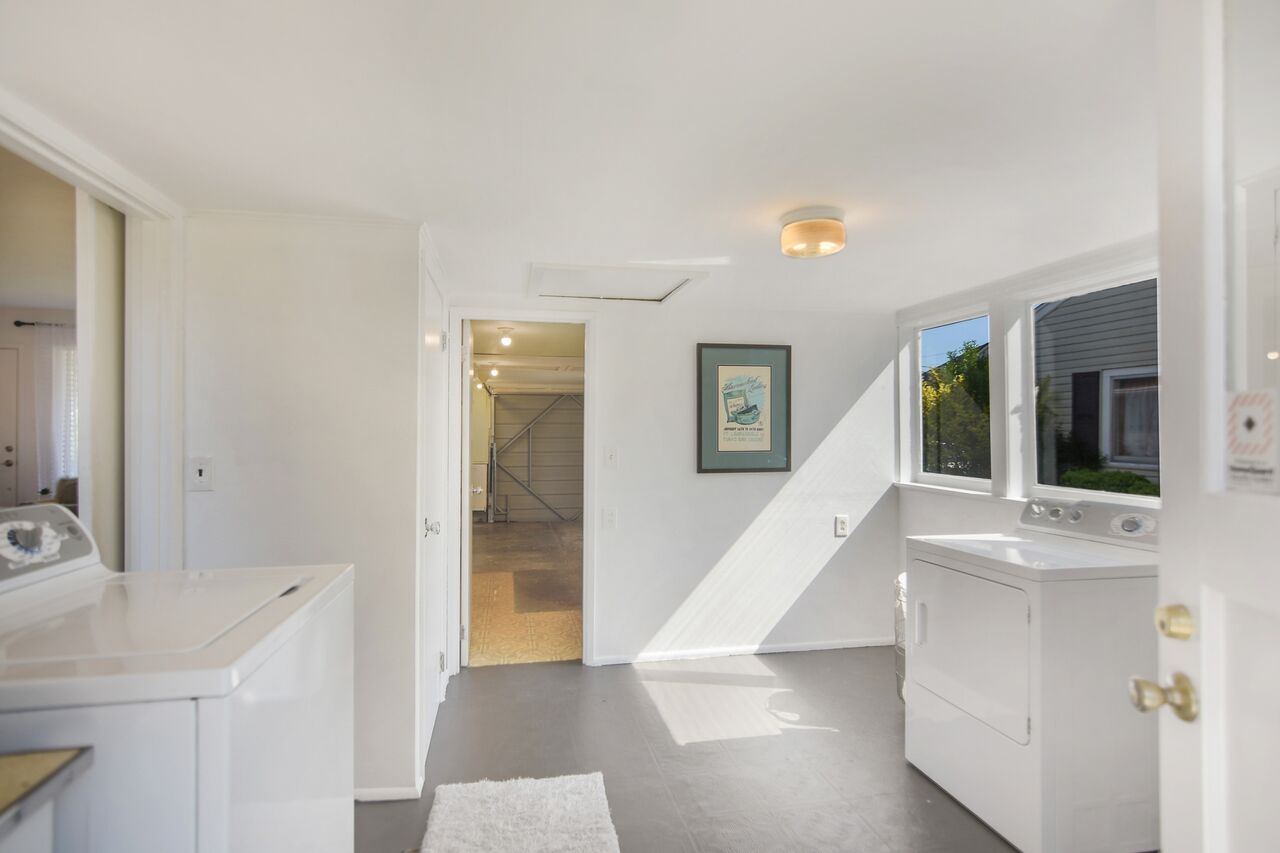 A well lit laundry room with a small counter and sink opens into the garage and has a back door to the patio.