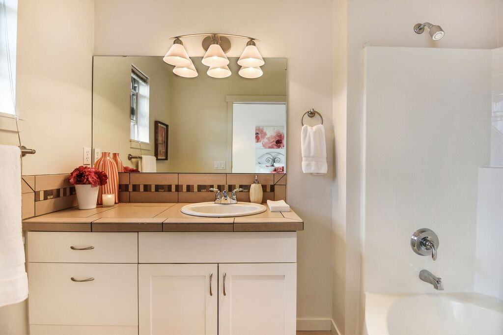 Oval tub and vanity with both cupboards and drawers in the suite's full bath.