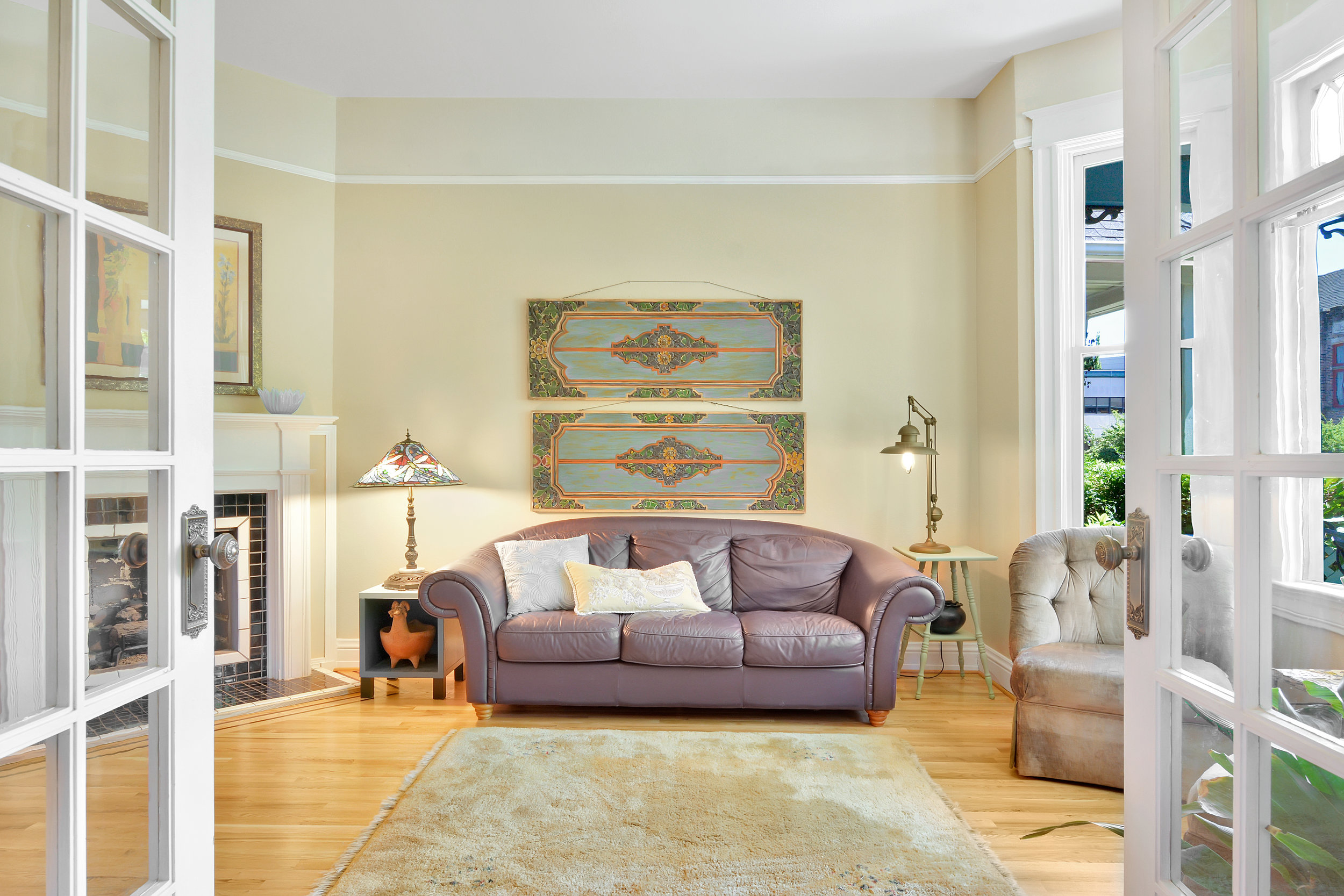Living room with bay windows, gas fireplace, glass door entry and picture rail.