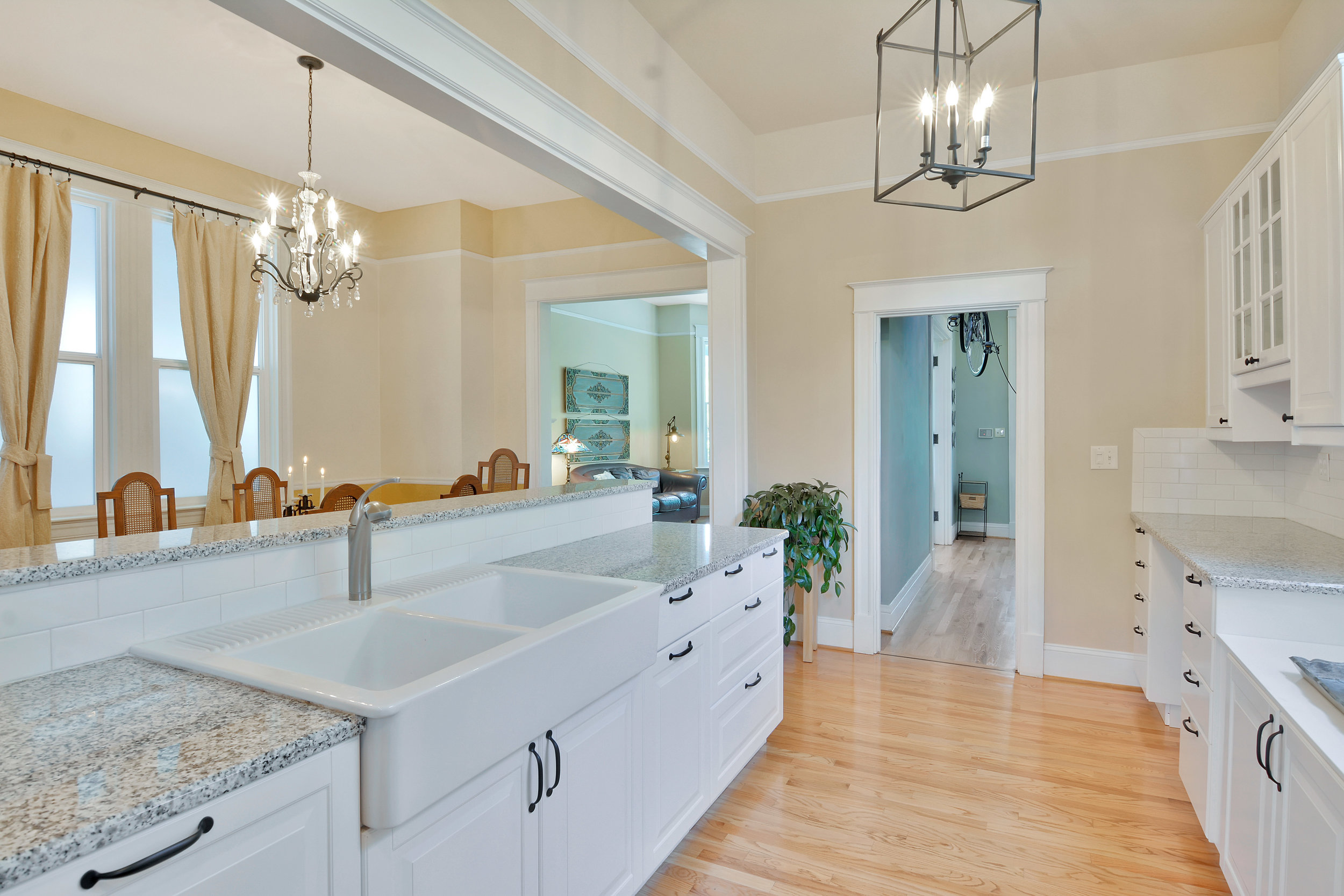 Updated kitchen with farmhouse sink, stone counters, and custom cabinets.
