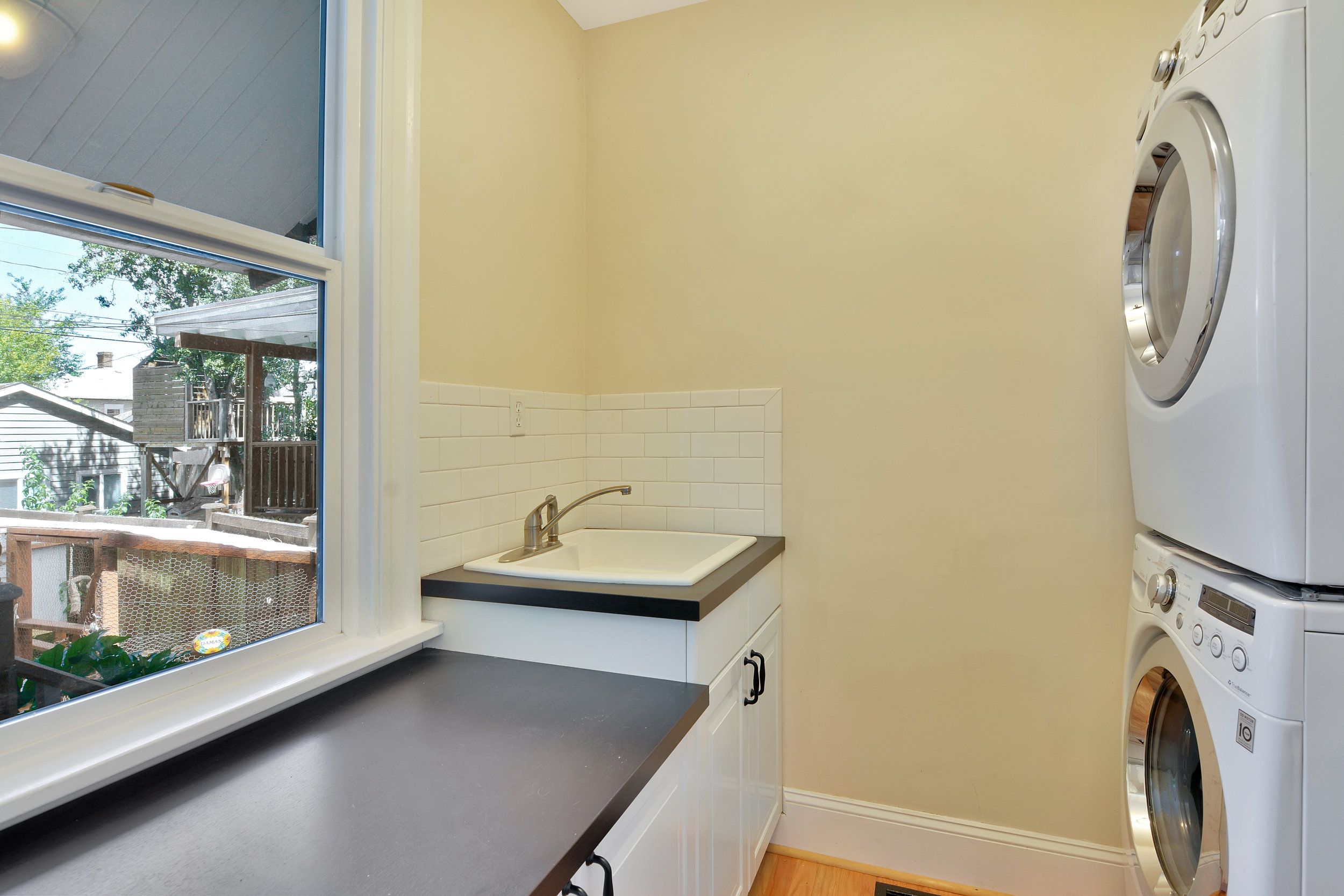 The laundry room includes a sink, clothes folding counter space, and a view to the back yard.