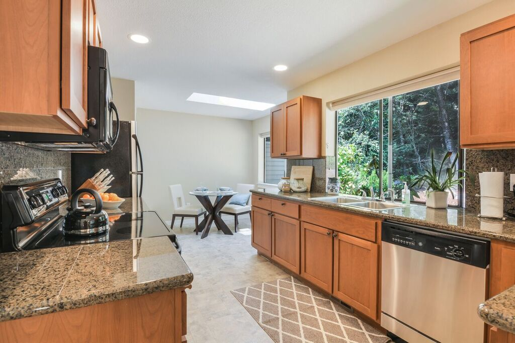 The kitchen is finished with granite tile counters, stainless appliances, a double sink, plenty of window light, a skylight, and a nice bar counter where you could pull up a set of stools.