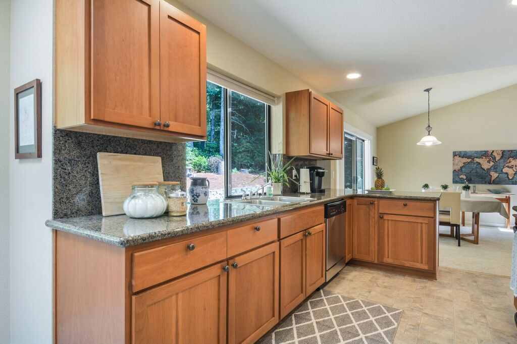 Easy to clean vinyl floor, big windows over the sink, and generous cabinets for storage.