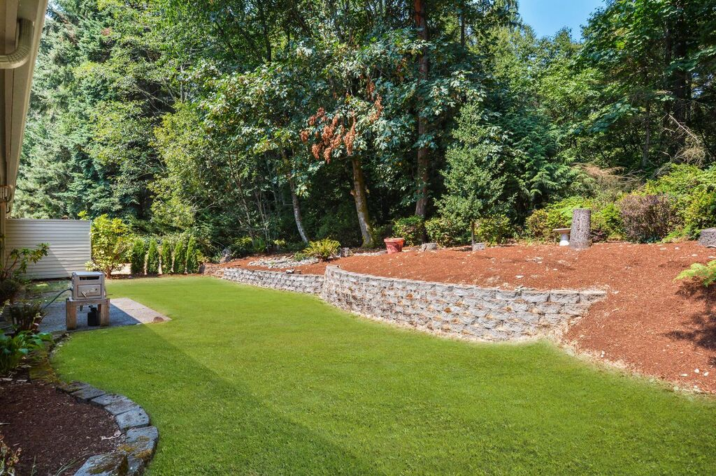 The back yard is bordered by maples, Douglas fir, cedar, alder, madrona, huckleberry bushes, and has a nice shape with the wall creating multiple levels.