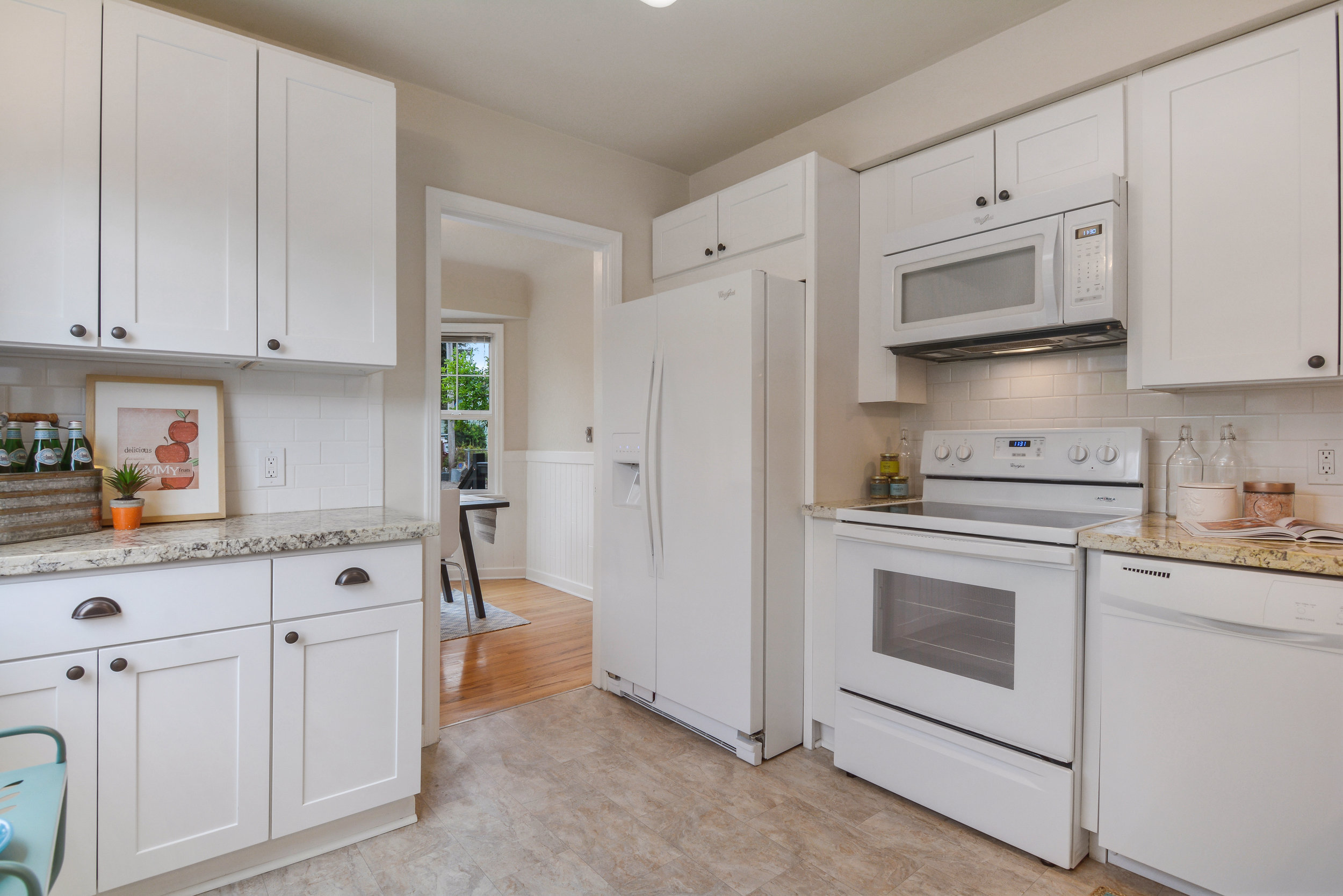 This kitchen is fitted with a neutral, easy to maintain vinyl floor that adds a touch of warmth to the clean, and sleek white of the subway tile backsplash, ample cabinets, and side-by-side refrigerator.