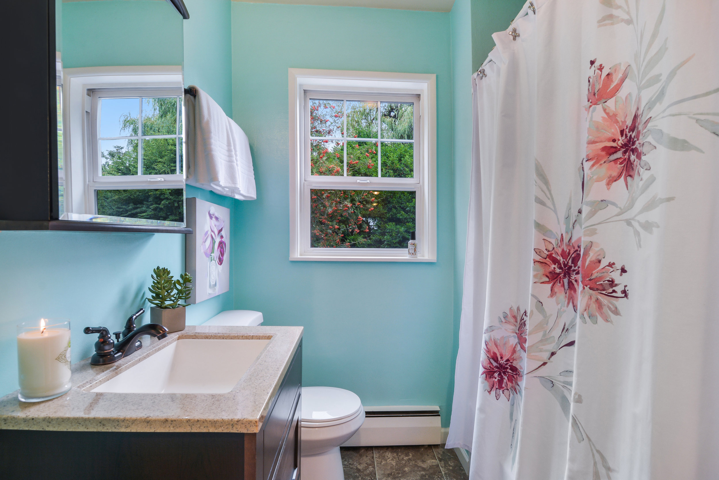 This full bath is located in the hall between the 2 main floor bedrooms. With a clean, white tub surround, contrasting hardware, and a view to the Mountain Ash tree in the backyard, this is a very pleasant and practical bathroom.