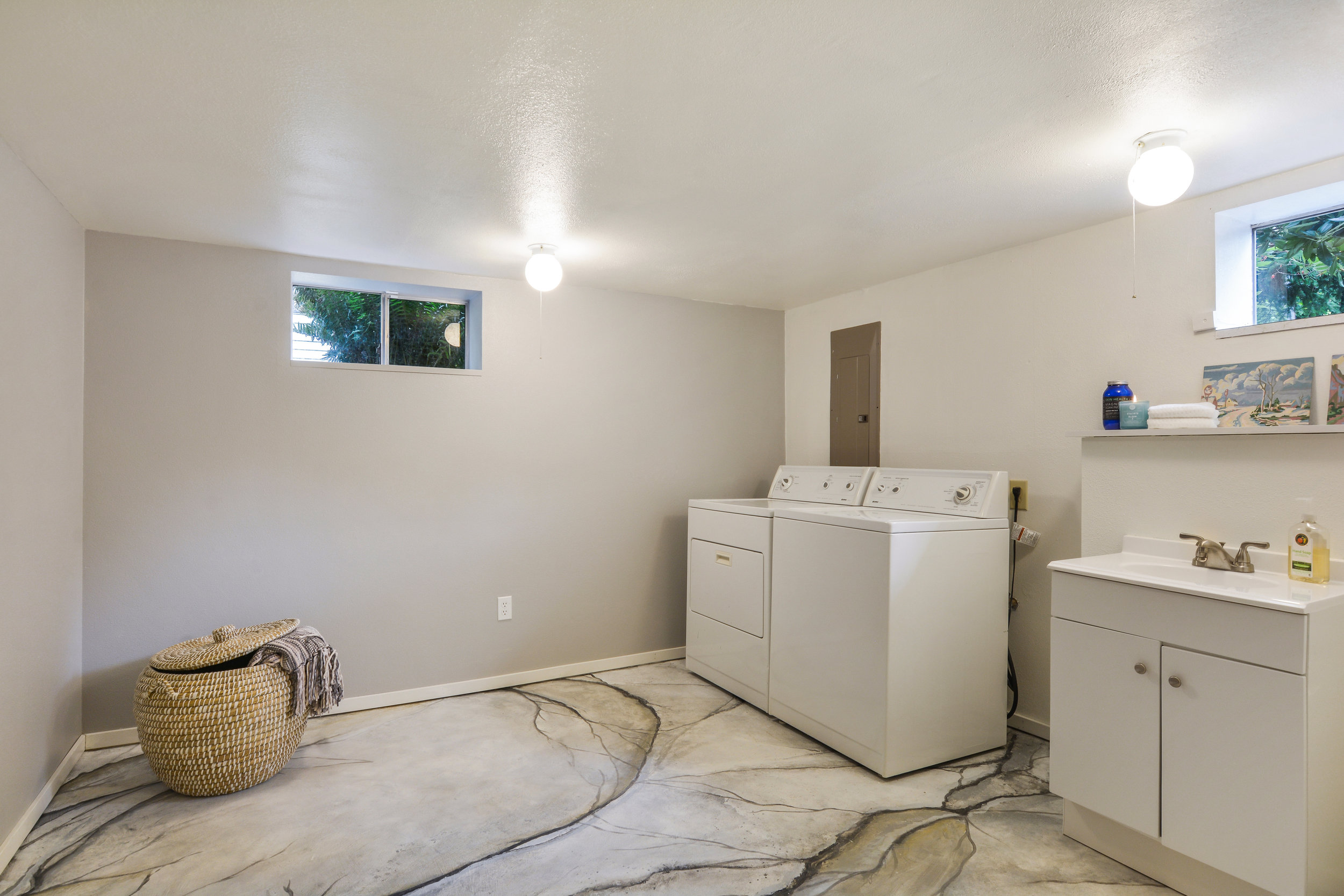 This laundry room, found at the base of the stairs is complete with a washer and dryer, lots of floor space, and a 3/4 bath.