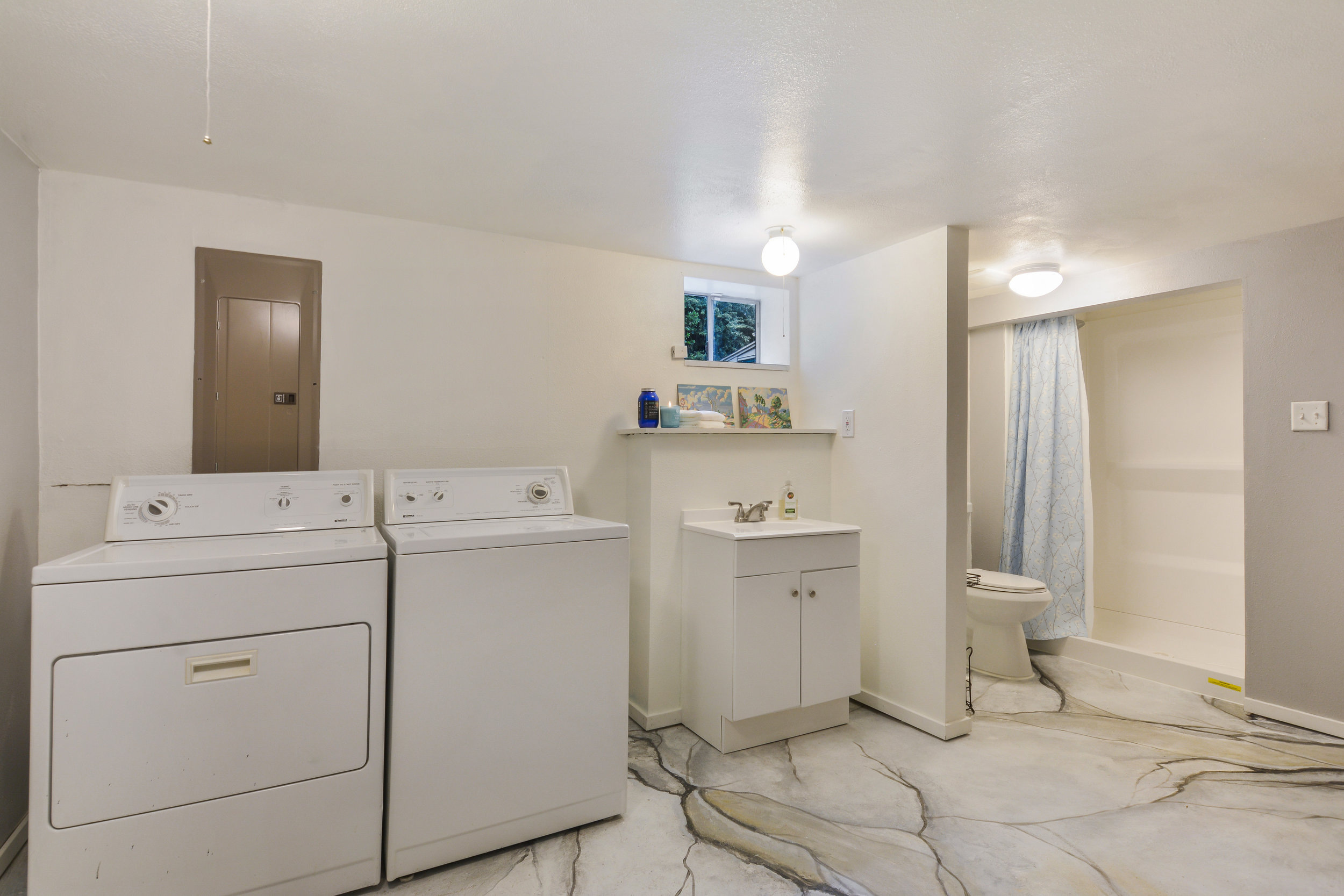 This convenient room includes a shower, toilet, and sink, as well as laundry. Add a table for folding laundry, or shelves along the wall. This room has the space for it.
