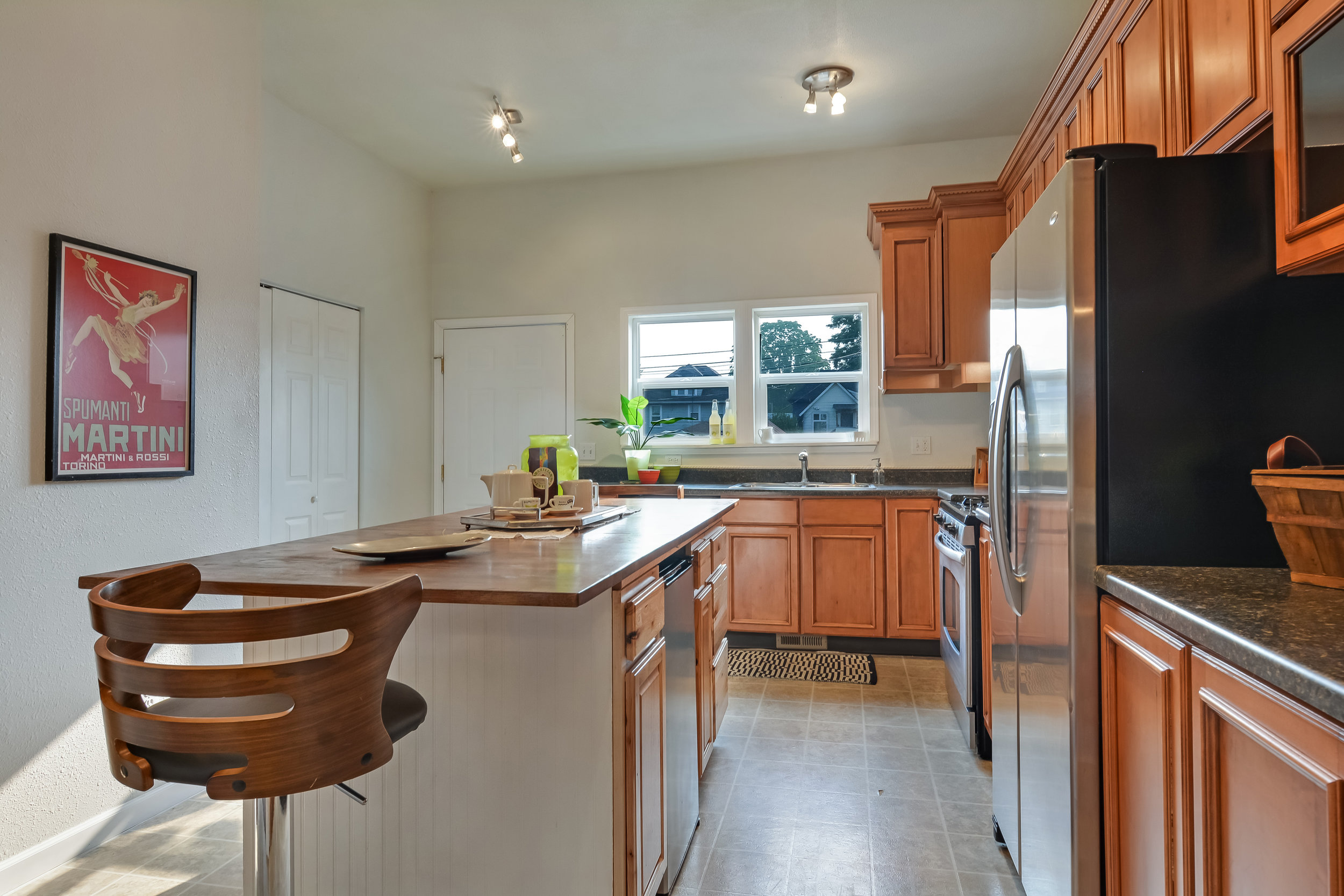 Another view of the custom kitchen island, this time with the mini fridge, perfect for beverages, in view. You'll also notice a door on the left. Inside are the washer and dryer.