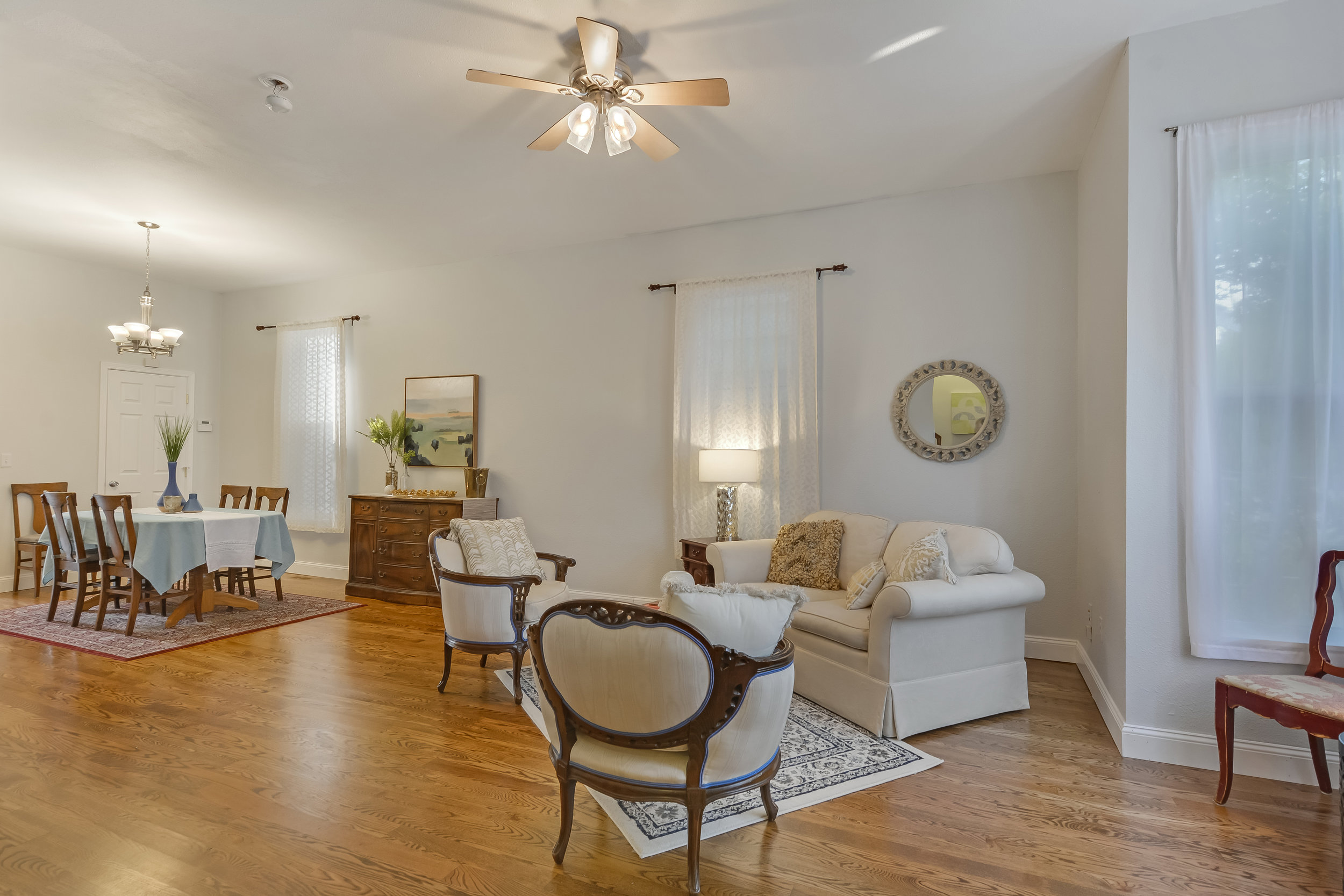The open living room is brightened by tall windows and kept comfortable all year with the air conditioning available throughout the house.