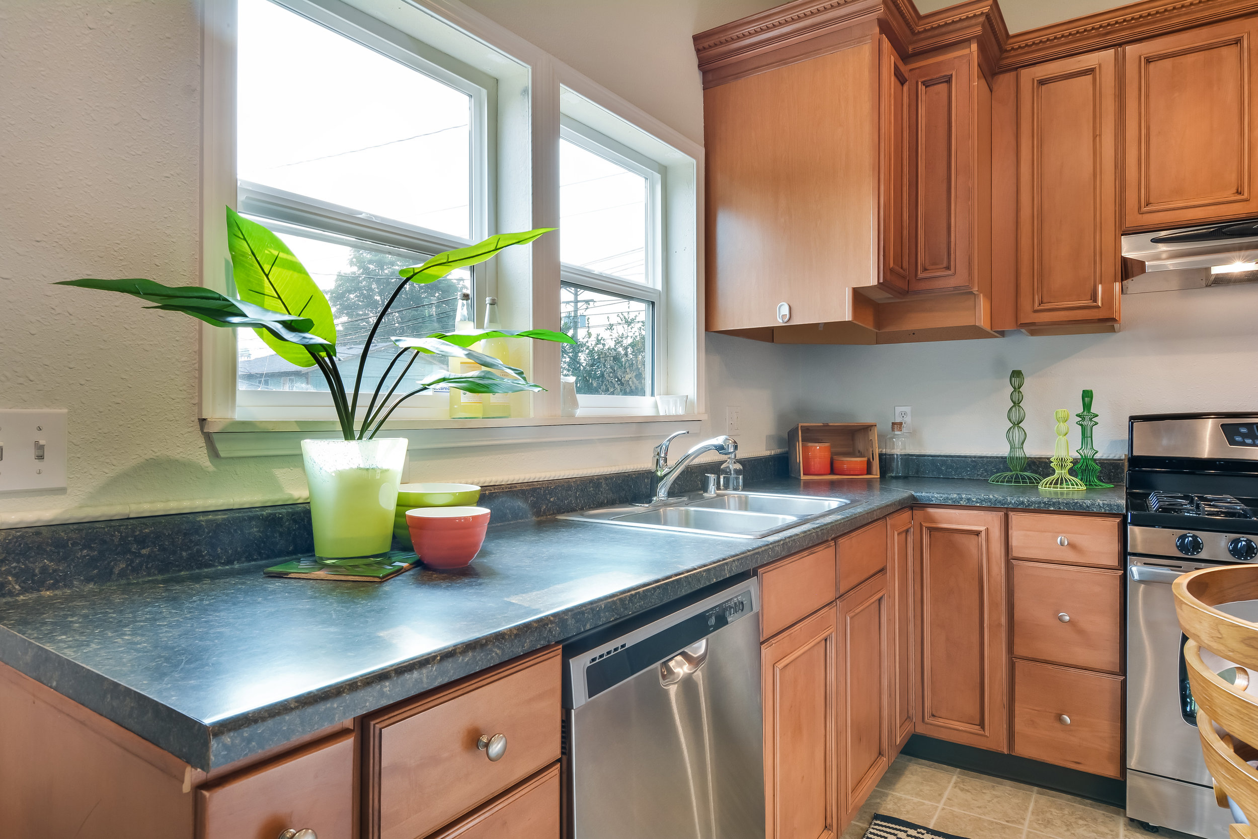 Stainless double sink and bright eastward facing windows look out over the back yard.