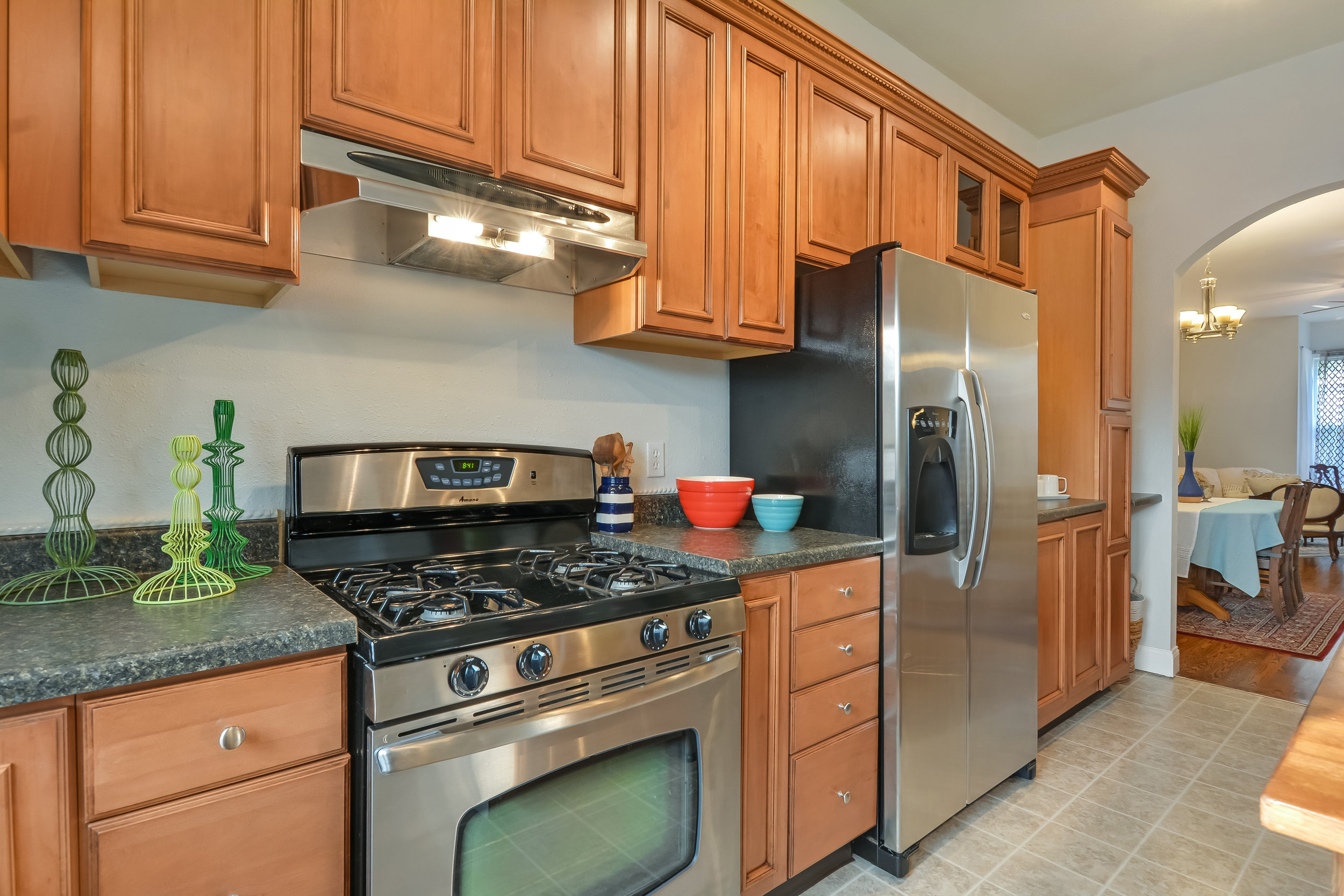 Gas stove, side-by-side refrigerator, and a peek at the glass front display cabinets just beyond the fridge.