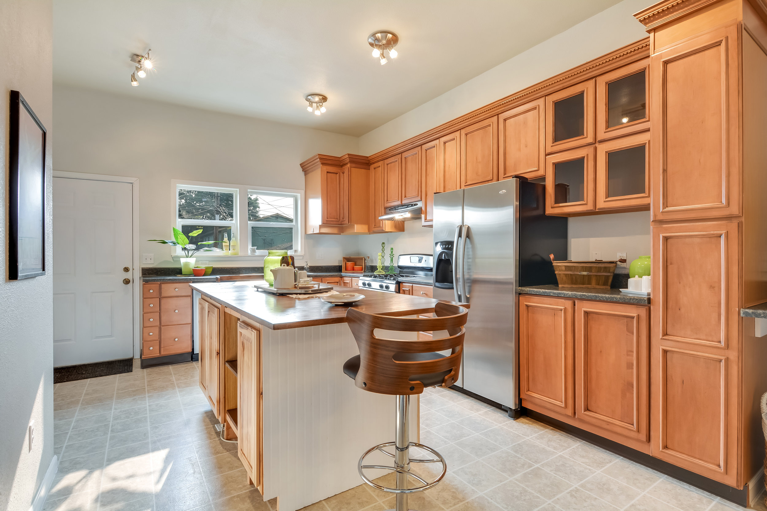 Updated kitchen includes this custom island with cabinets made of acacia wood. The top of the island is reclaimed from an artist's office in Portland, and there's even a mini fridge tucked in there!