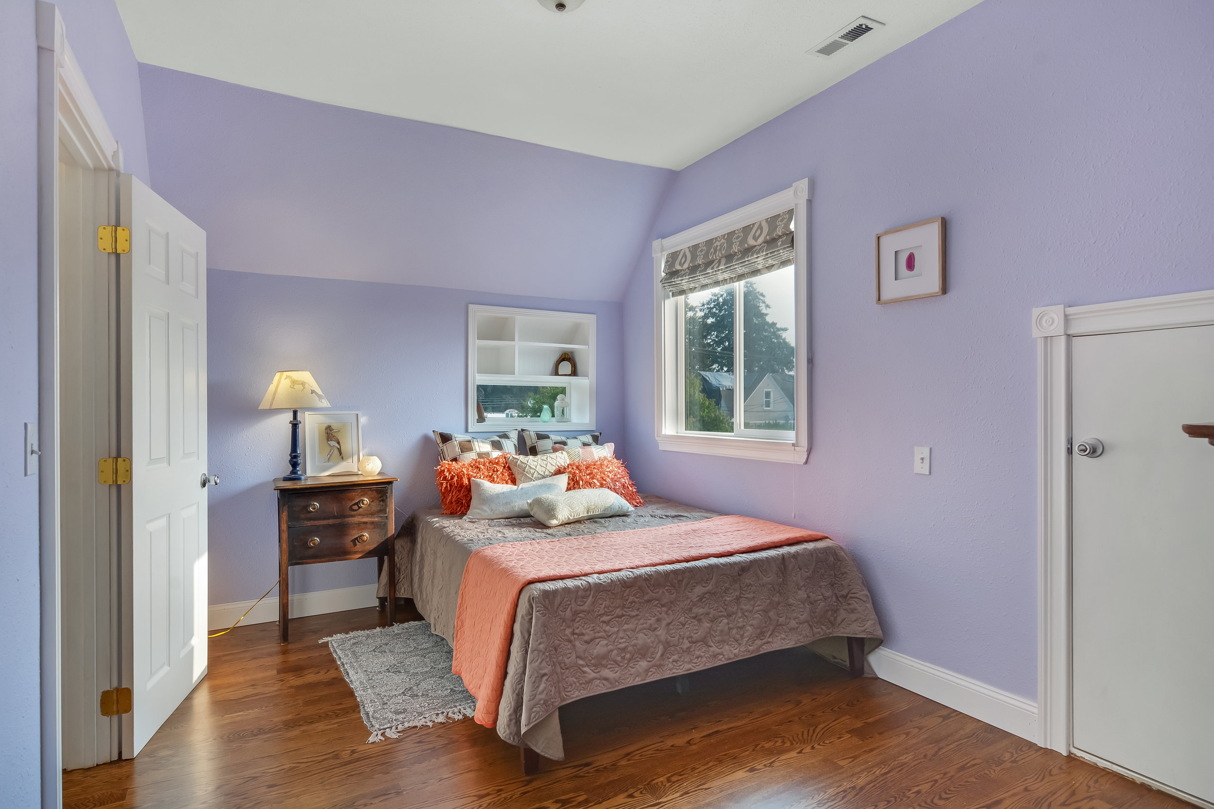 The second upstairs bedroom includes a door into a storage area (on the right). Don't miss the built-in shelf and tiny window above the head of the bed. So pretty!
