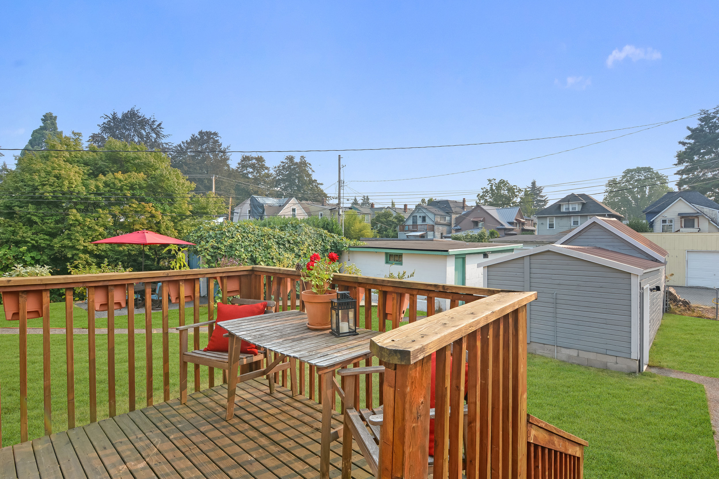 Another view of the back deck perfect for a little table and pots of herbs or flowers. Lawn below, and the single car garage on the alley.