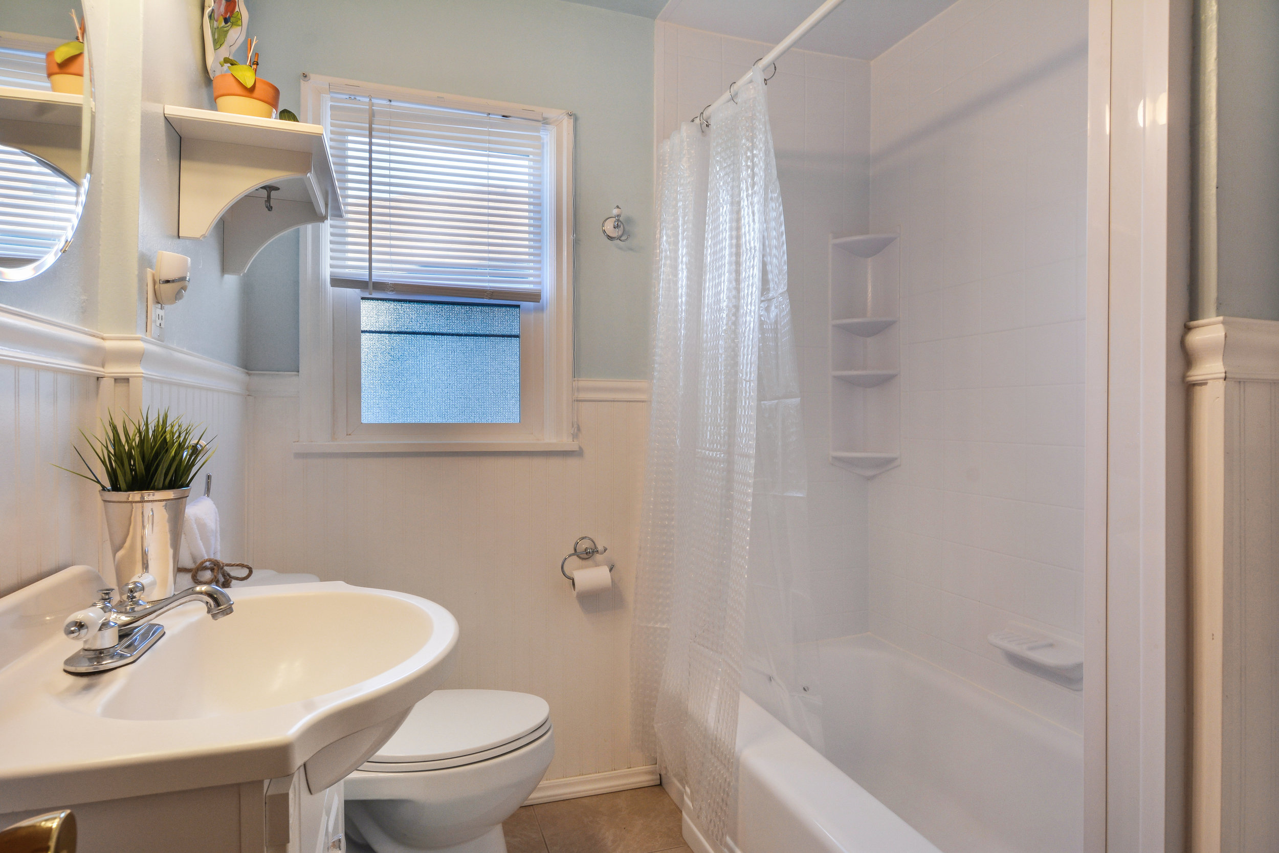 The full bathroom is located between the two bedrooms in a spacious hall. Tile floor, easy to clean tub surround, white wainscot, and cool color scheme.
