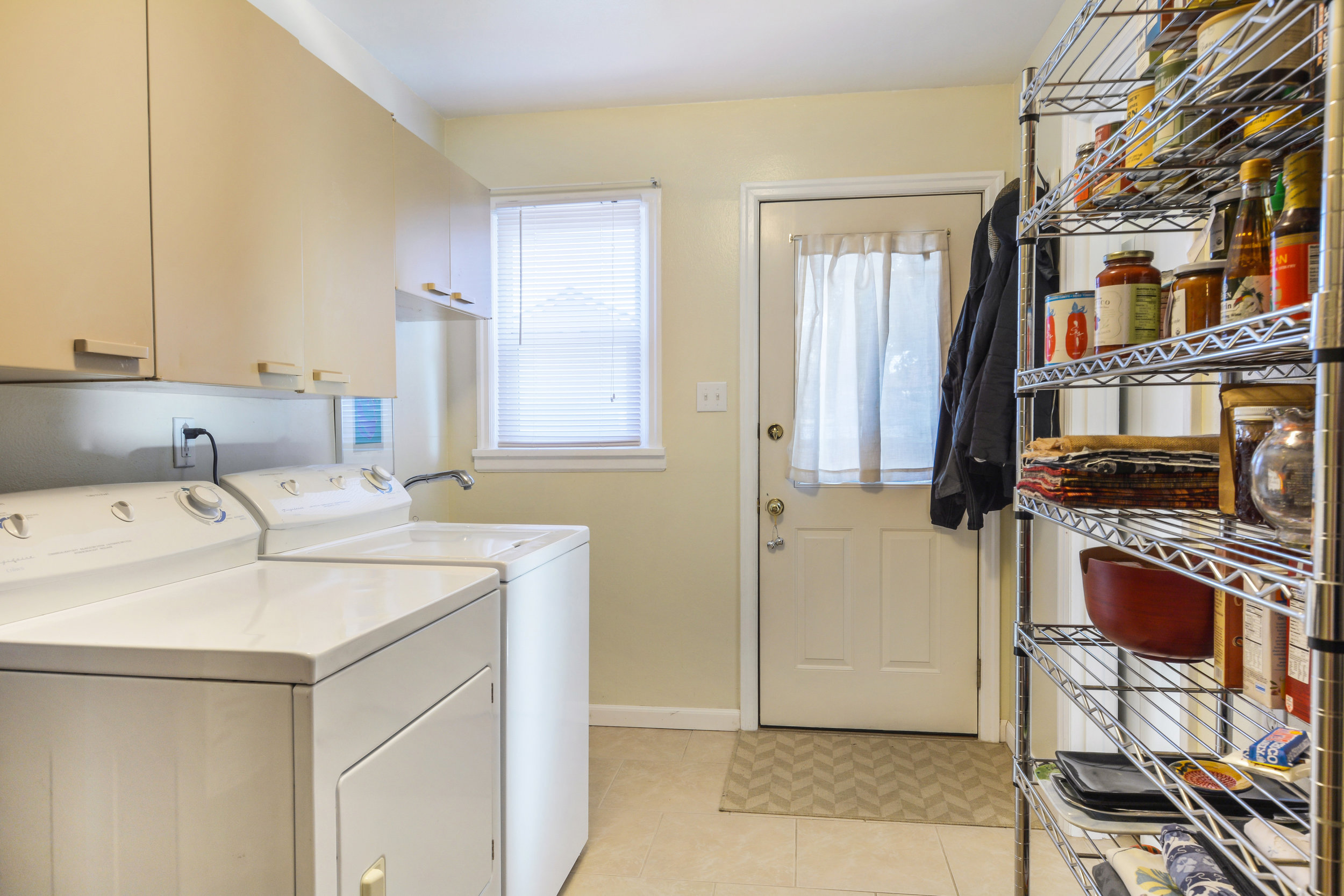 With additional cabinets, pantry shelves, and a utility sink, this room provides helpful storage and function to the home.