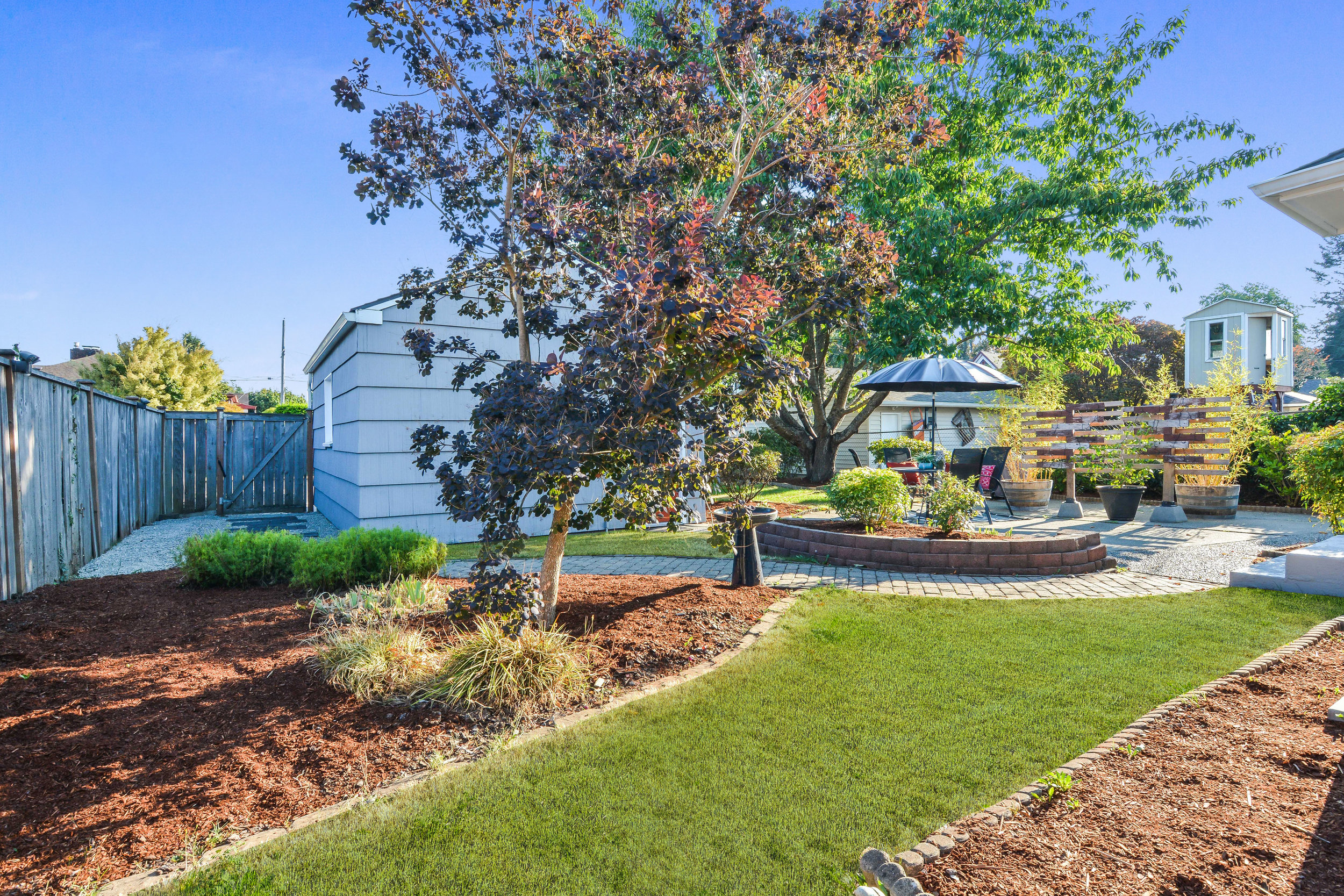 Lawn space, landscaped beds, and pretty trees surround the paved patio in this fully fenced backyard.