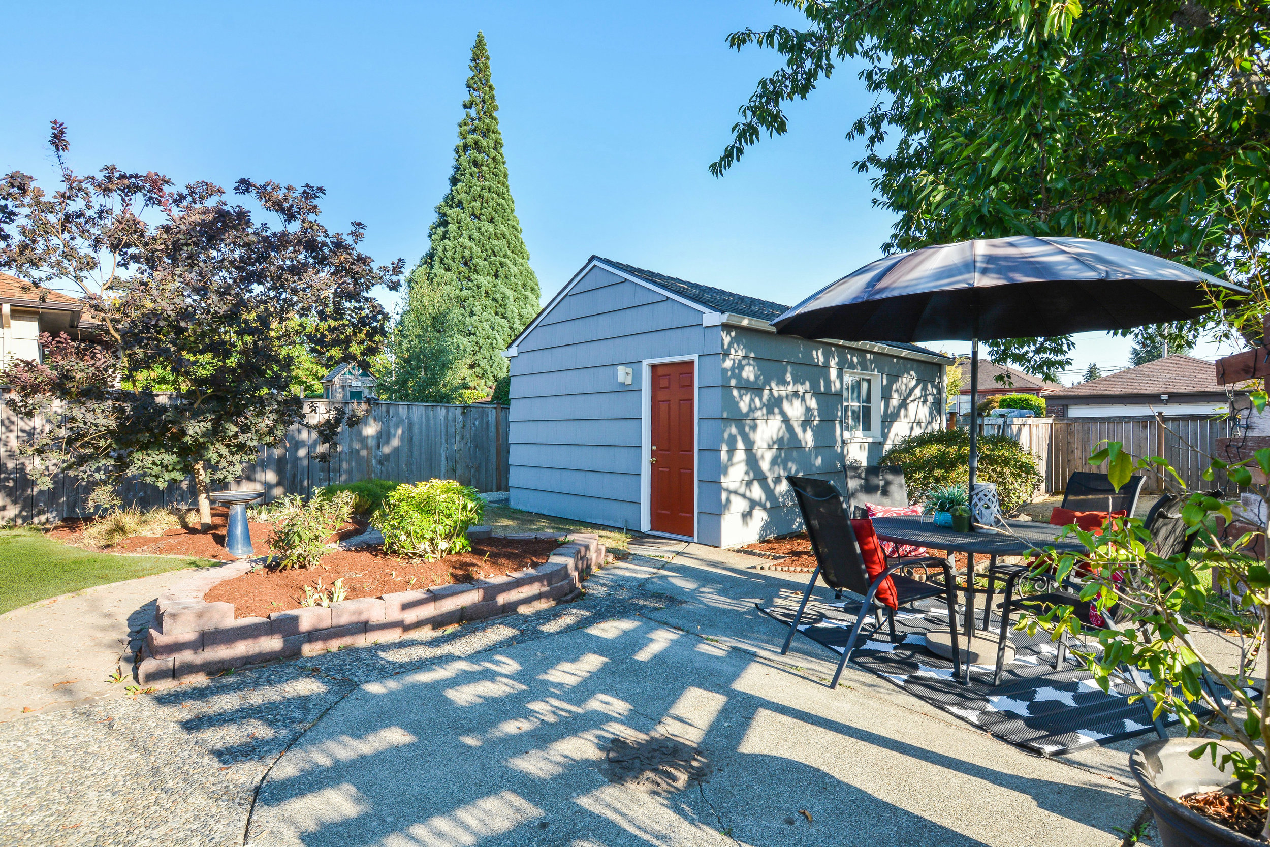 A view of the fully fenced and beautifully landscaped back yard with its patio, paved pathways, fruiting cherry tree, lawn space, smoke tree, and detached garage on the paved alley.